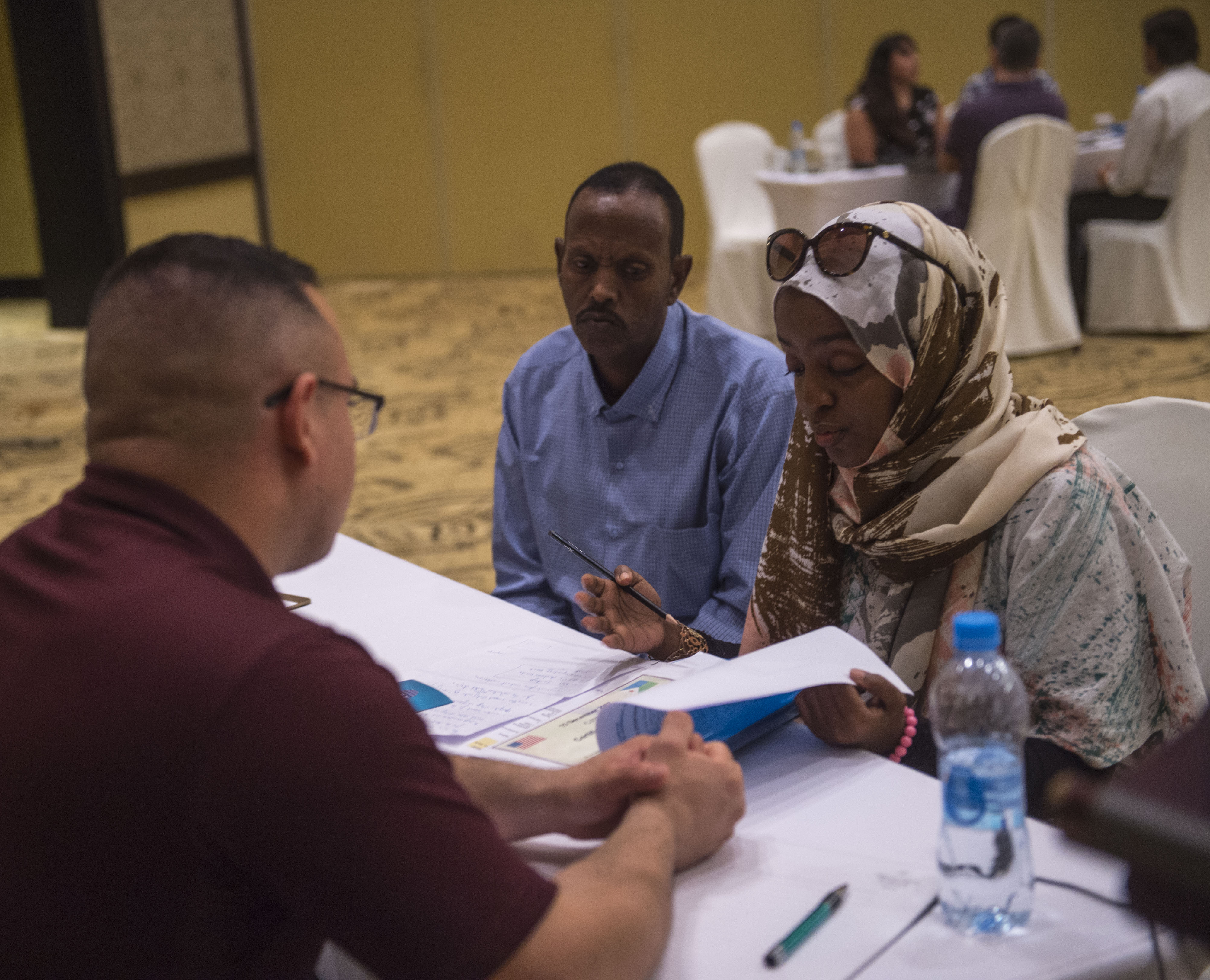 U.S. Army Staff Sgt. Uriel Ramirez, Combined Joint Task Force - Horn of Africa (CJTF-HOA) Contingency Contracting Office (CCO) contracting officer, talks with representatives from a local business during a Djibouti Economic Outreach Symposium in Ilon Du Heron, Djibouti, Dec. 19, 2017. Hosted by the CJTF-HOA CCO and commonly referred to as Vendor Day, the symposium is designed to get local business owners together and make them aware of the opportunities and process of doing business as a vendor with the U.S. government. (U.S. Air Force photo by Staff Sgt. Timothy Moore)