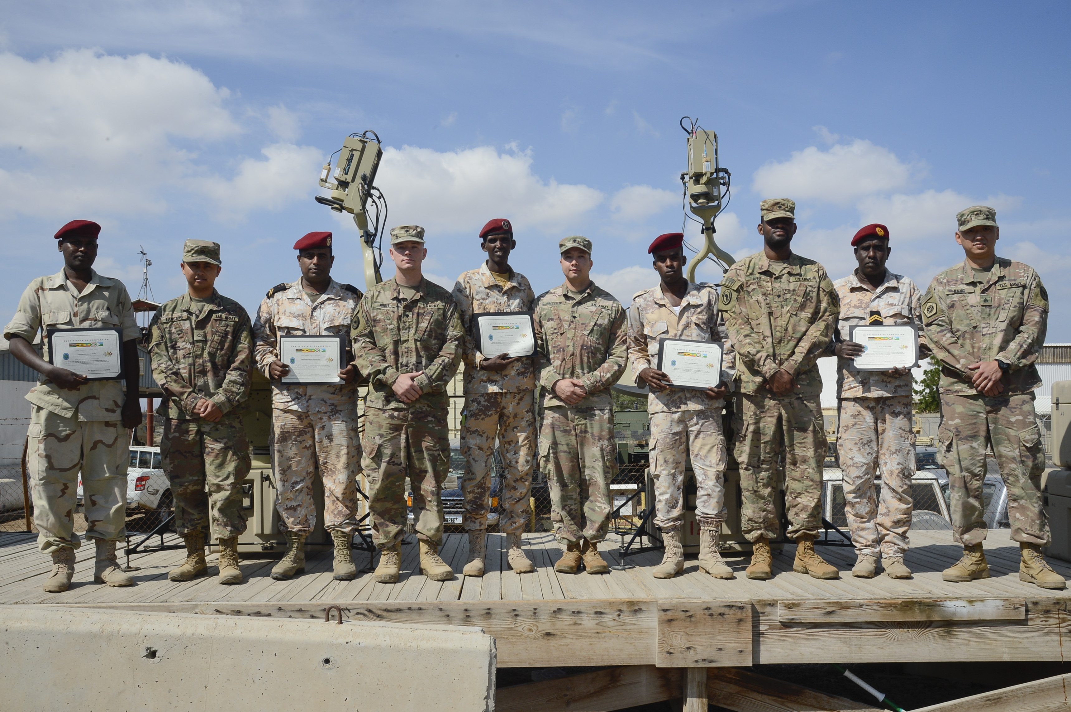U.S. Soldiers assigned to the Combined Joint Task Force - Horn of Africa (CJTF-HOA) Communications Directorate and members of the Djibouti Armed Forces pose for a photo after completing a military-to-military exchange course at Camp Lemonnier, Djibouti, Jan. 17, 2018. Throughout a two-week period, communications experts advised Djiboutian service members on how to set up, operate, maintain, and troubleshoot network equipment to increase communication capabilities between African Union Mission in Somalia forces. (U.S. Navy photo by Mass Communication Specialist 2nd Class Timothy M. Ahearn)