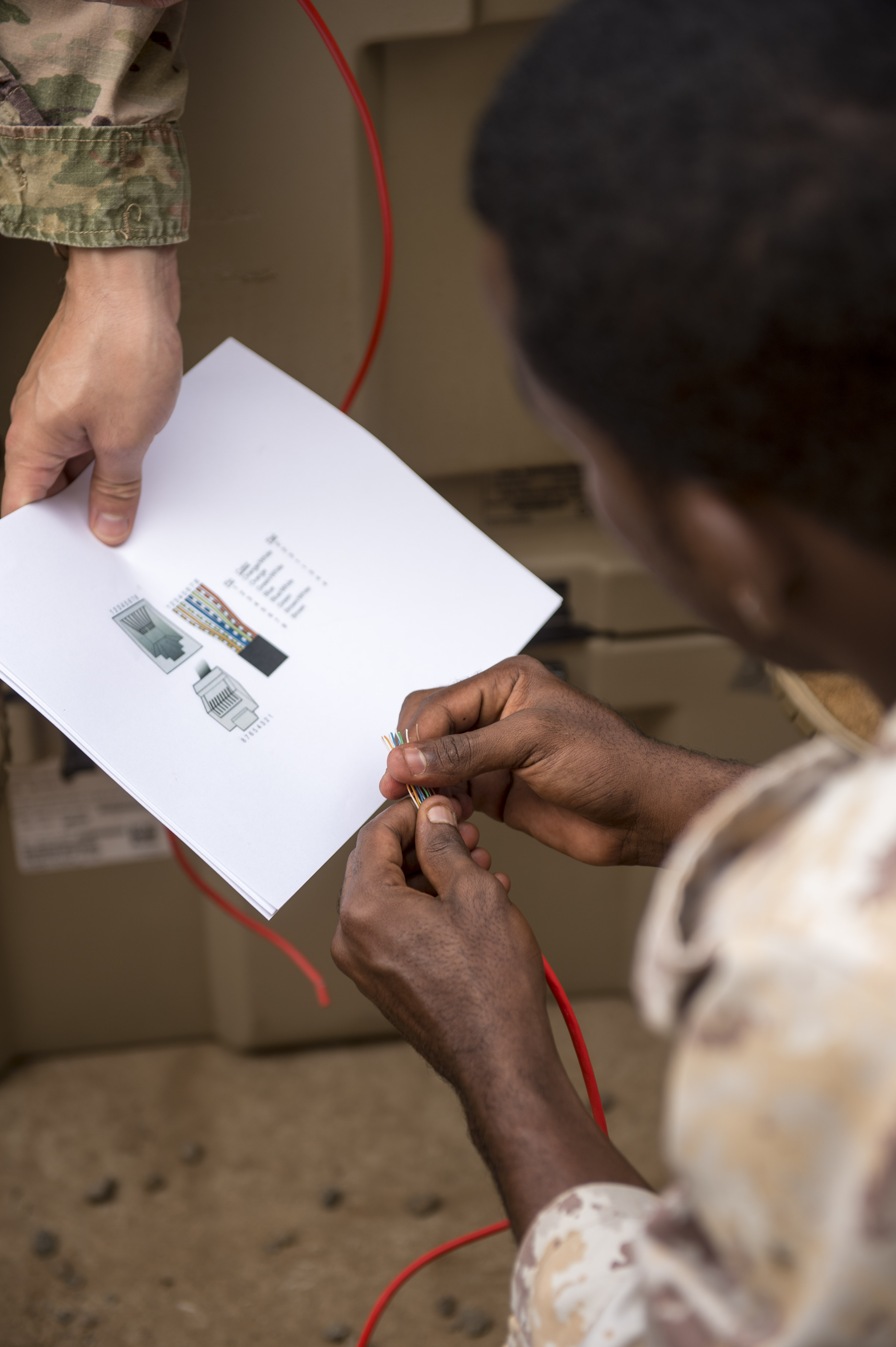 A Djibouti Armed Forces (FAD) member reviews a guide to set up the wires for a cable during a military-to-military exchange course with U.S. Soldiers assigned to the Combined Joint Task Force - Horn of Africa (CJTF-HOA) Communications Directorate, at Camp Lemonnier, Djibouti, Jan. 10, 2018. Throughout a two-week period, communications experts advised Djiboutian service members on how to set up, operate, maintain, and troubleshoot network equipment to increase communication capabilities between African Union Mission in Somalia forces. (U.S. Air Force photo by Staff Sgt. Timothy Moore)