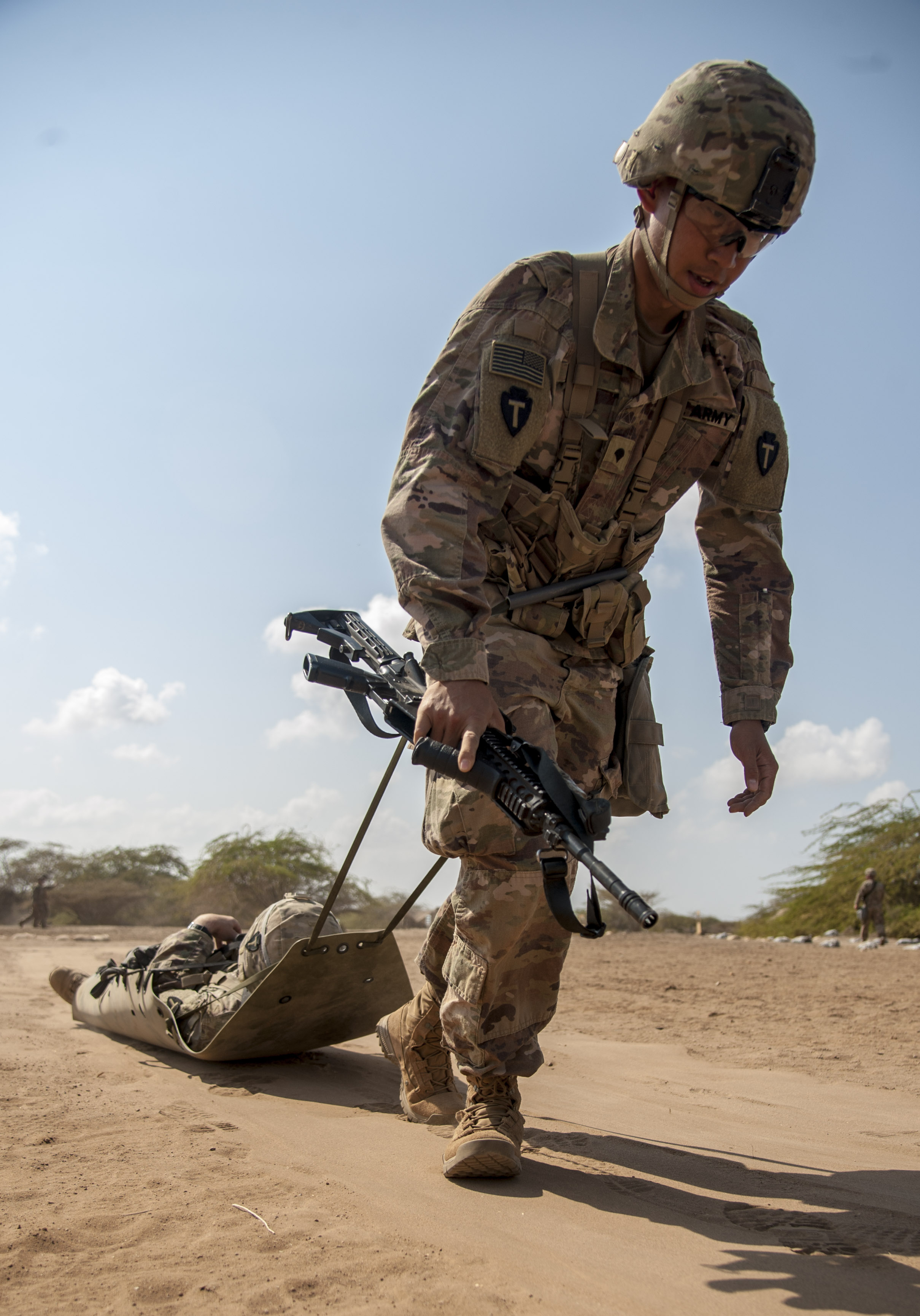 A U.S. Army Soldier assigned to Combined Joint Task Force - Horn of Africa practices the Objective Bull, a task that requires the evacuation and treatment of a casualty, in preparation for an Expert Infantryman Badge (EIB) evaluation at Camp Lemonnier, Djibouti, Jan. 22, 2018. The EIB is a coveted special skills badge that requires infantry Soldiers to pass a five-day evaluation that consists of an Army Physical Fitness Test, day and night land navigation, a 12-mile forced march, and 30 individual tasks covering weapons, medical, and security patrol skills. In an April 2016 EIB iteration at Camp Lemonnier, only 15 percent of candidates earned the badge. (U.S. Air Force photo by Staff Sgt. Timothy Moore)
