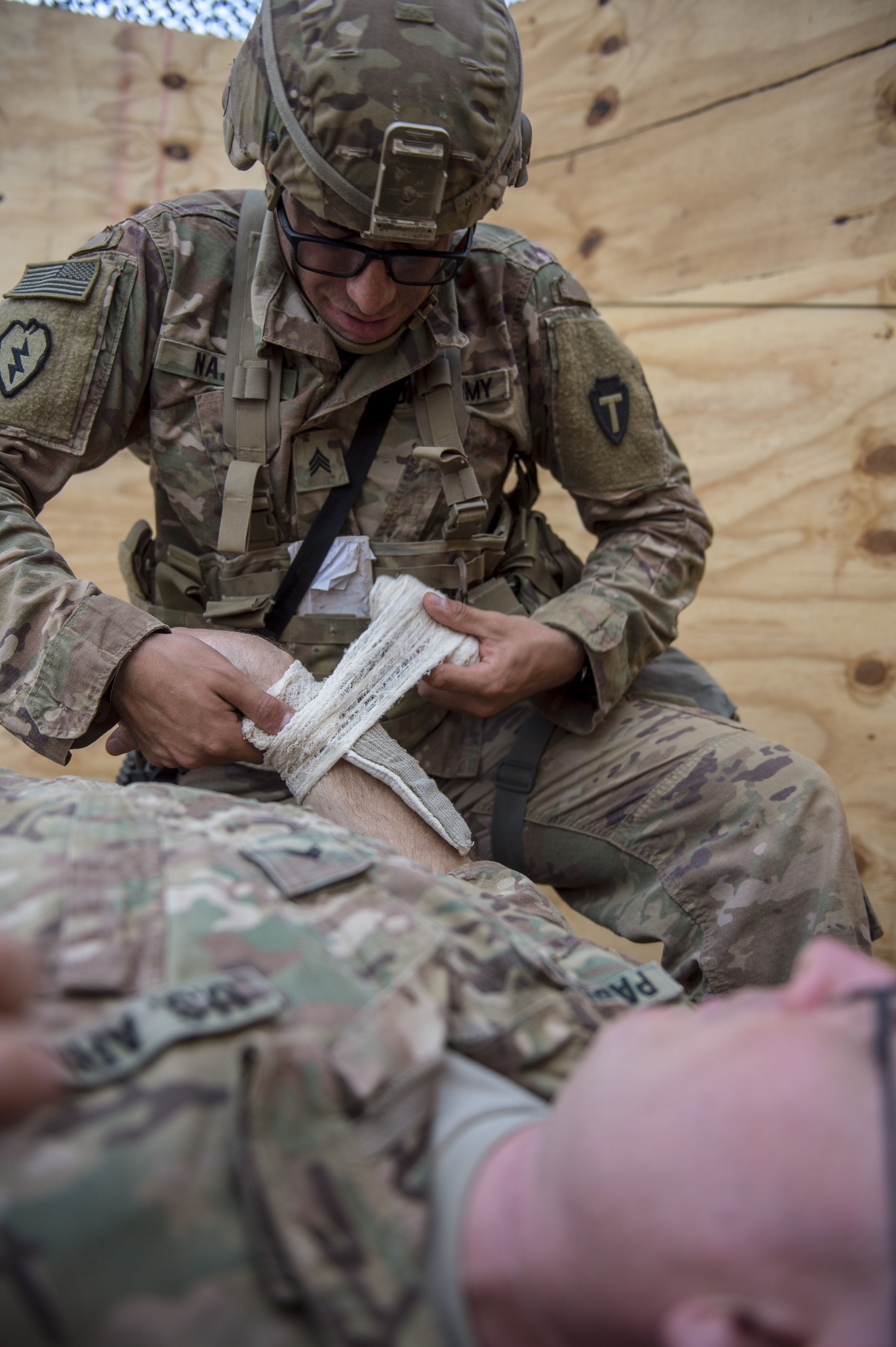 A U.S. Army Soldier assigned to Combined Joint Task Force - Horn of Africa wraps a bandage around a simulated burn wound of a casualty during training for an Expert Infantryman Badge (EIB) evaluation at Camp Lemonnier, Djibouti, Jan. 24, 2018. The EIB is a coveted special skills badge that requires infantry Soldiers to pass a five-day evaluation that consists of an Army Physical Fitness Test, day and night land navigation, a 12-mile forced march, and 30 individual tasks covering weapons, medical, and security patrol skills. In an April 2016 EIB iteration at Camp Lemonnier, only 15 percent of candidates earned the badge. (U.S. Air Force photo by Staff Sgt. Timothy Moore)