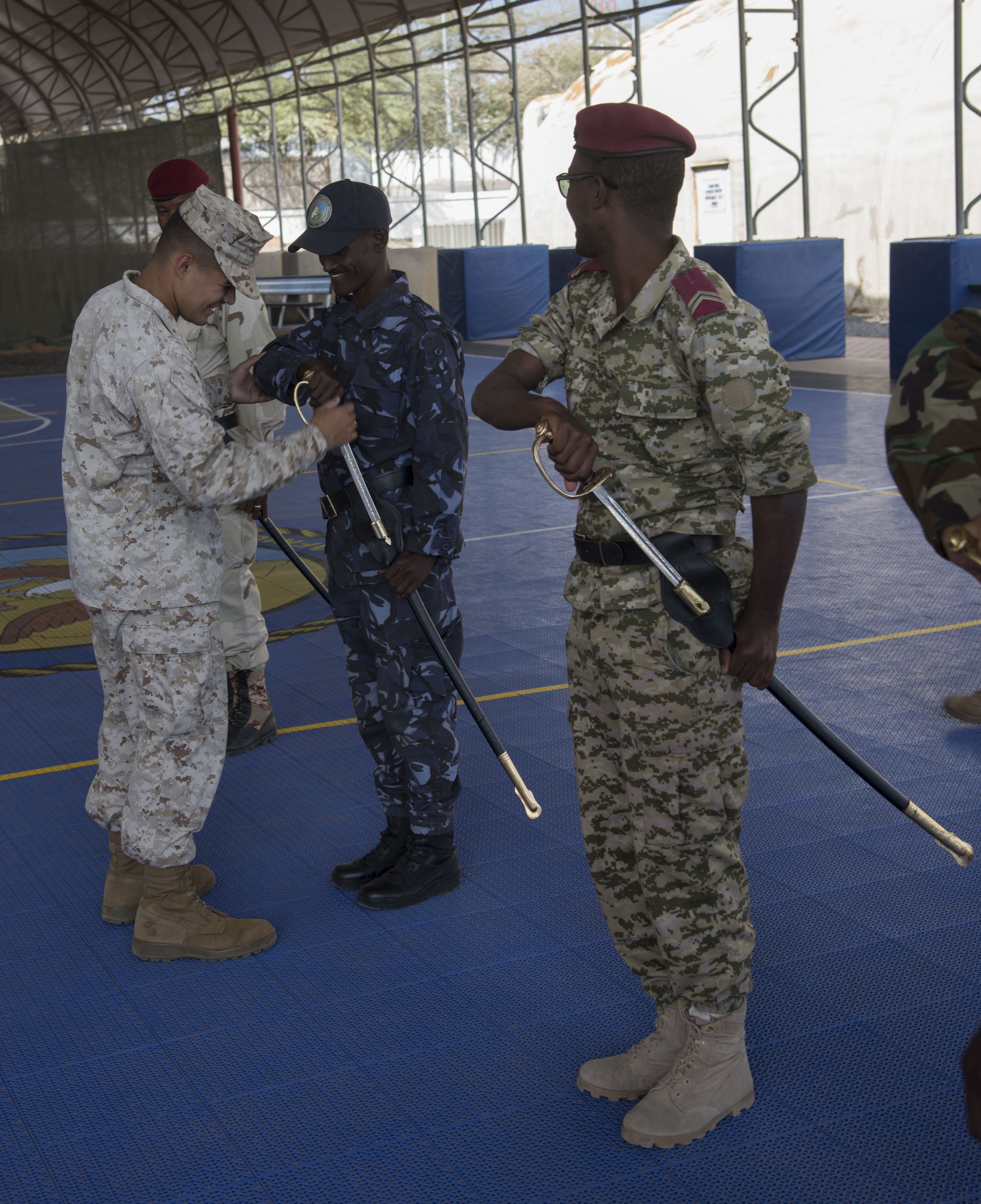 U.S. Marine Corps Sgt. Raymundo Rodriguez shows a Djiboutian military member the proper arm position during sword and guidon training as part of a Joint Corporals Course hosted by Combined Joint Task Force – Horn of Africa at Camp Lemonnier, Jan. 12, 2018. The Joint Corporals Course is designed to provide junior service members with the knowledge and skills necessary to assume leadership roles of greater responsibility as a non-commissioned officer, as well as strengthen bonds between participating militaries. (U.S. Air National Guard photo by Staff Sgt. Allyson L. Manners)