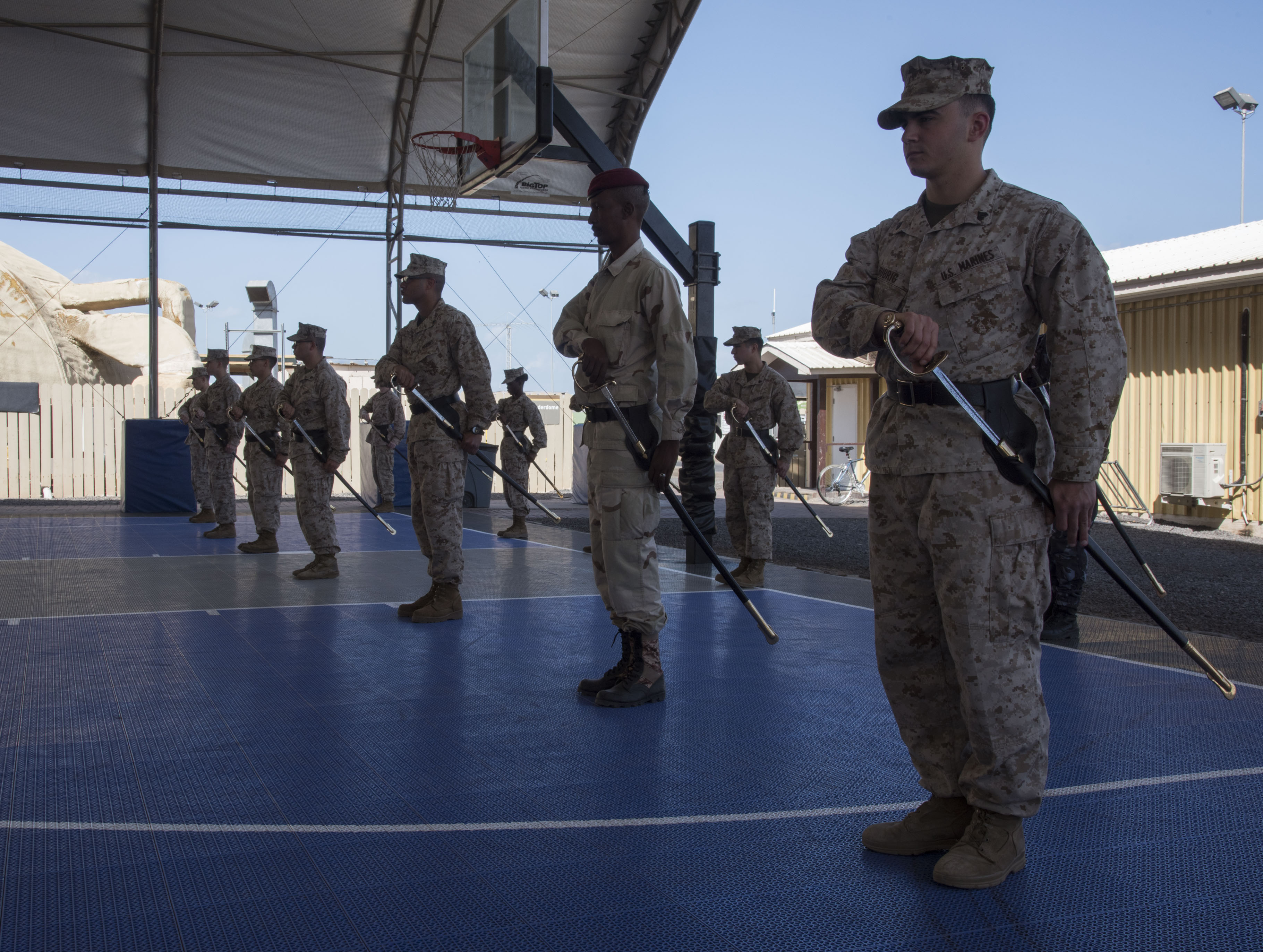U.S. Marines and Djiboutian military members prepare for the order to present their swords during sword and guidon training as part of a Joint Corporals Course hosted by Combined Joint Task Force – Horn of Africa at Camp Lemonnier, Jan. 12, 2018. The Joint Corporals Course is designed to provide junior service members with the knowledge and skills necessary to assume leadership roles of greater responsibility as a non-commissioned officer, as well as strengthen bonds between participating militaries. (U.S. Air National Guard photo by Staff Sgt. Allyson L. Manners)