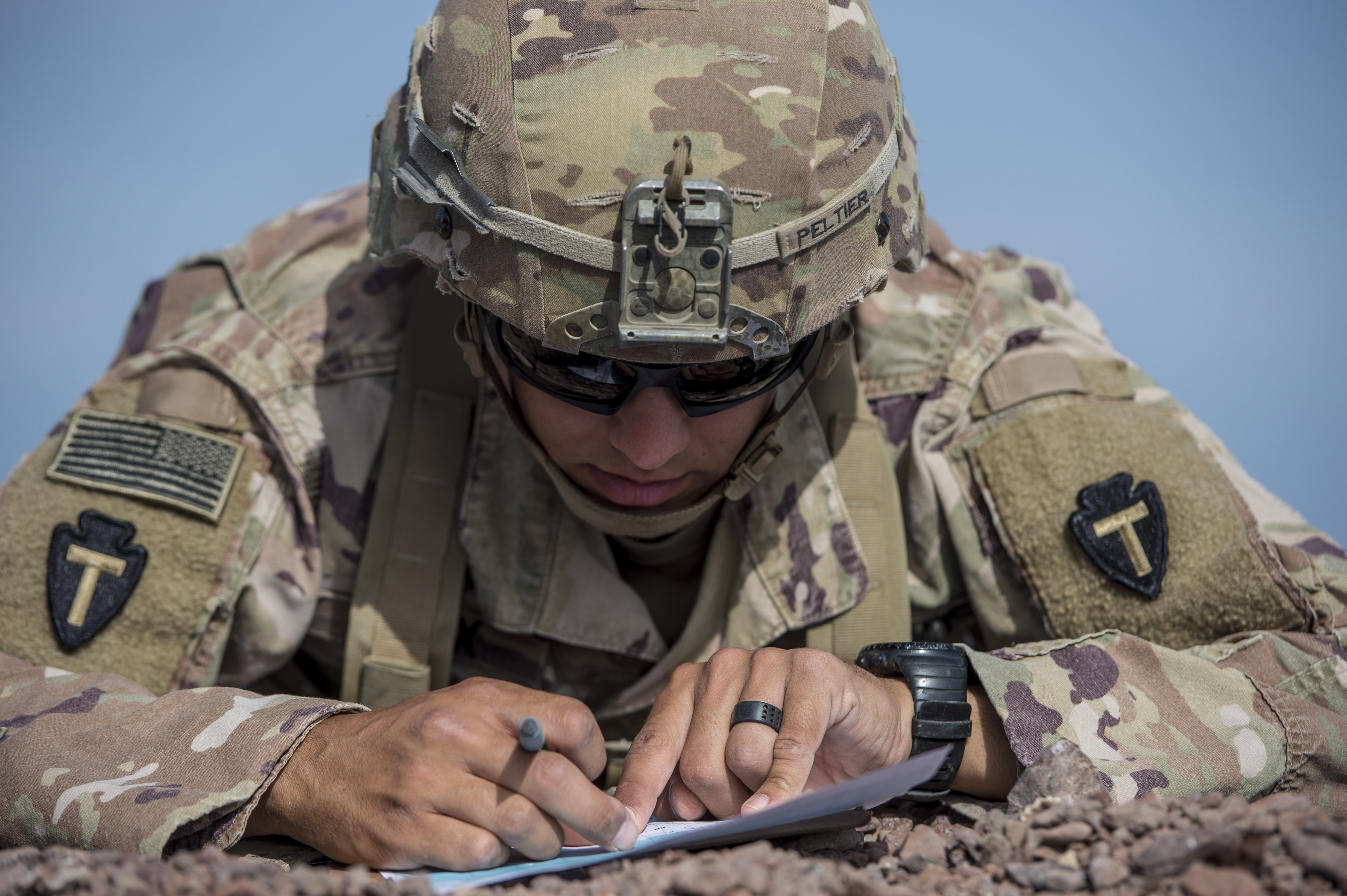 A U.S. Army Soldier assigned to Combined Joint Task Force - Horn of Africa plots a grid point during land navigation training in preparation for an Expert Infantryman Badge evaluation at Arta Range, Djibouti, Jan. 25, 2018. After two weeks of training and five days of testing, 50 Soldiers completed the process to earn the coveted special skills badge that requires Soldiers to perform an Army Physical Fitness Test, day and night land navigation, a 12-mile forced march, and 30 individual tasks covering weapons, medical, and security patrol skills. (U.S. Air Force photo by Staff Sgt. Timothy Moore)
