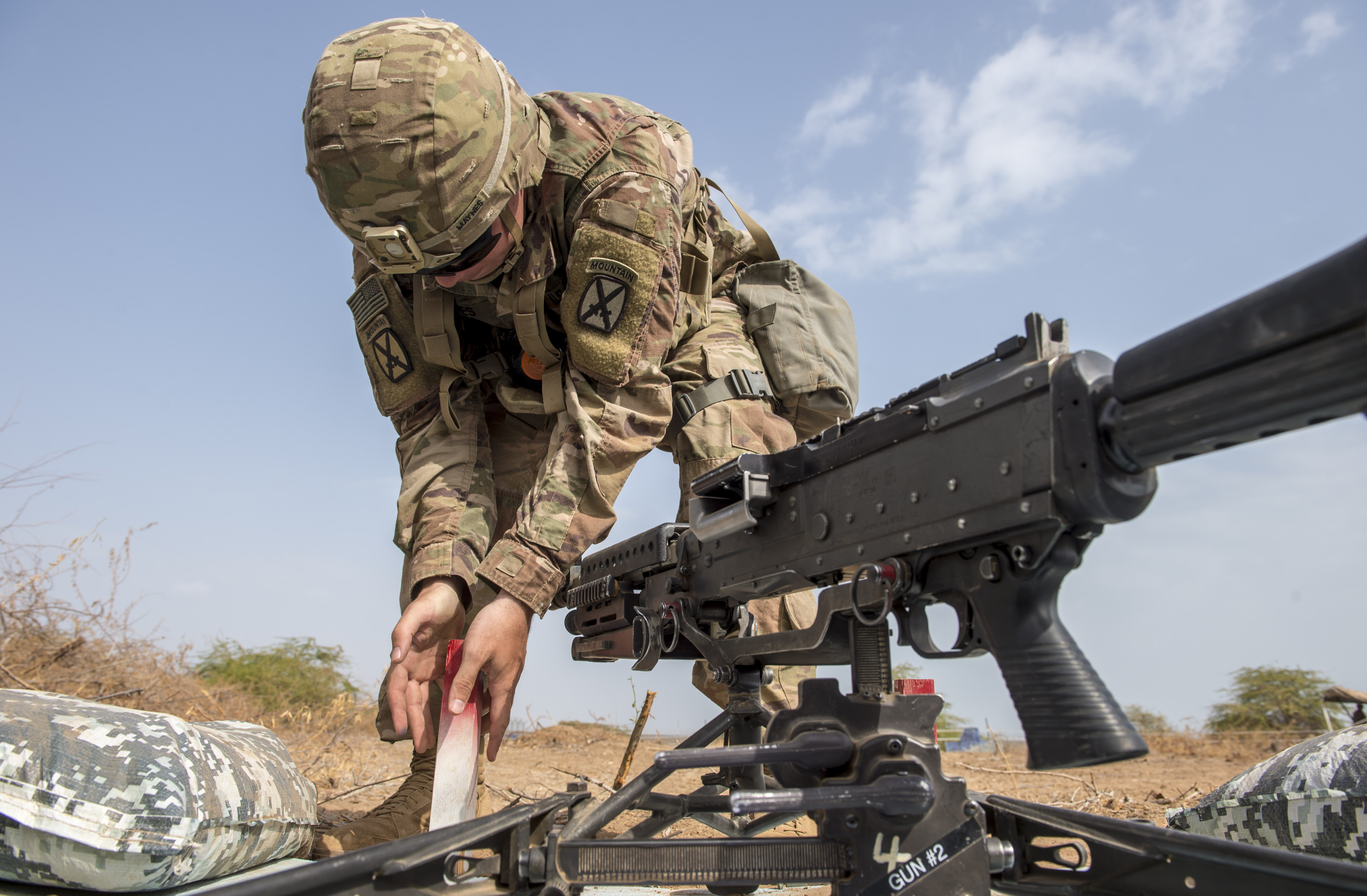 A U.S. Army Soldier assigned to Combined Joint Task Force - Horn of Africa puts a firing stake in the ground for a mounted M240B machine gun during training for an Expert Infantryman Badge evaluation at Camp Lemonnier, Djibouti, Jan. 24, 2018. The stake is used as a reference point for the firing zone as he prepares to set up a defensive position. After two weeks of training and five days of testing, 50 Soldiers completed the process to earn the coveted special skills badge that requires Soldiers to perform an Army Physical Fitness Test, day and night land navigation, a 12-mile forced march, and 30 individual tasks covering weapons, medical, and security patrol skills. (U.S. Air Force photo by Staff Sgt. Timothy Moore)