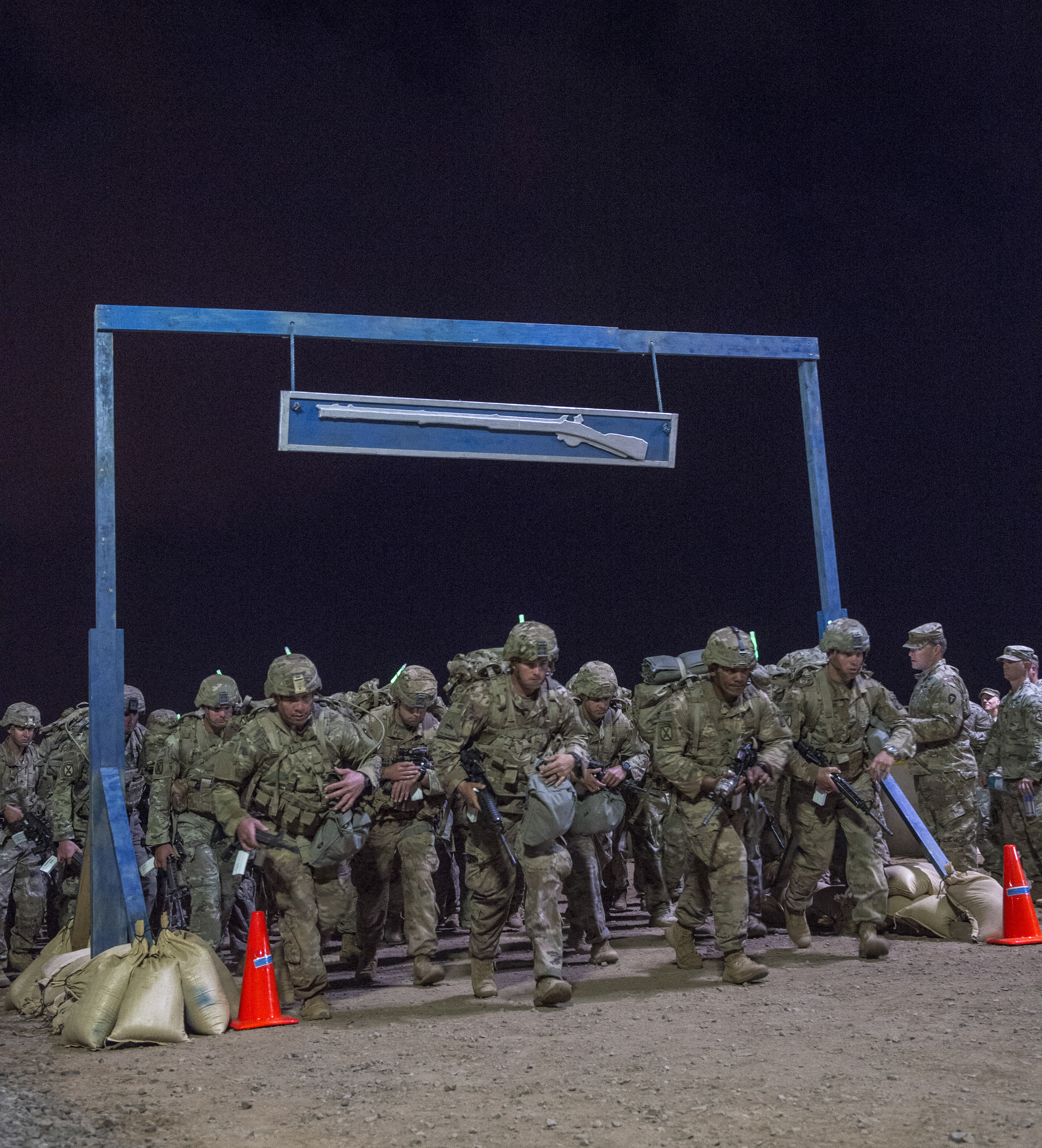 U.S. Army Soldiers assigned to Combined Joint Task Force - Horn of Africa begin the 12-mile march during an Expert Infantryman Badge evaluation at Camp Lemonnier, Djibouti, Feb. 2, 2018. After two weeks of training and five days of testing, 50 Soldiers completed the process to earn the coveted special skills badge that requires Soldiers to perform an Army Physical Fitness Test, day and night land navigation, a 12-mile forced march, and 30 individual tasks covering weapons, medical, and security patrol skills. (U.S. Air Force photo by Staff Sgt. Timothy Moore)