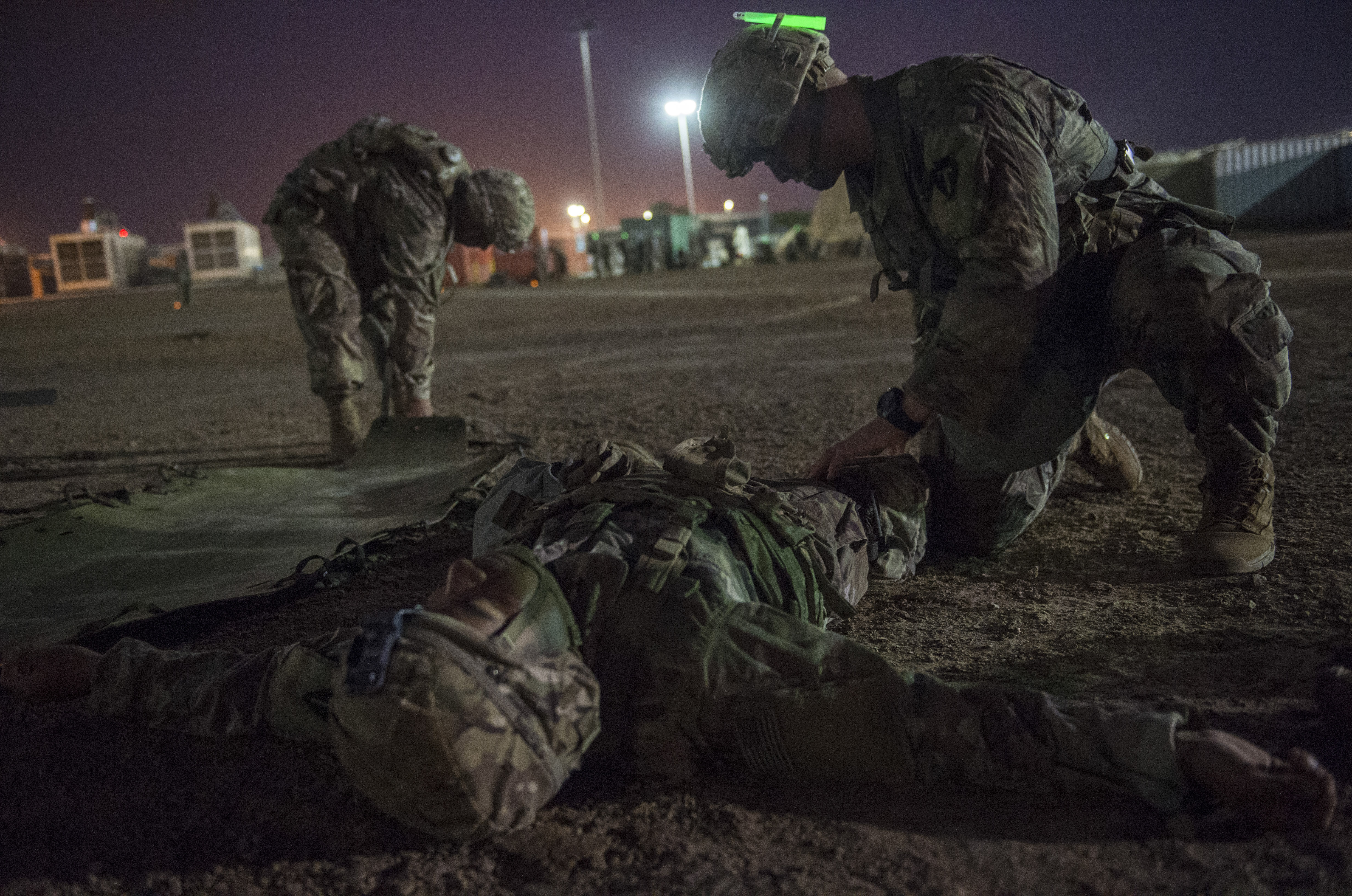 A U.S. Army Soldier assigned to Combined Joint Task Force - Horn of Africa applies a tourniquet to a simulated casualty during a task that requires the evacuation and treatment of a casualty, part of an Expert Infantryman Badge evaluation at Camp Lemonnier, Djibouti, Feb. 2, 2018. After two weeks of training and five days of testing, 50 Soldiers completed the process to earn the coveted special skills badge that requires Soldiers to perform an Army Physical Fitness Test, day and night land navigation, a 12-mile forced march, and 30 individual tasks covering weapons, medical, and security patrol skills. (U.S. Air Force photo by Staff Sgt. Timothy Moore)