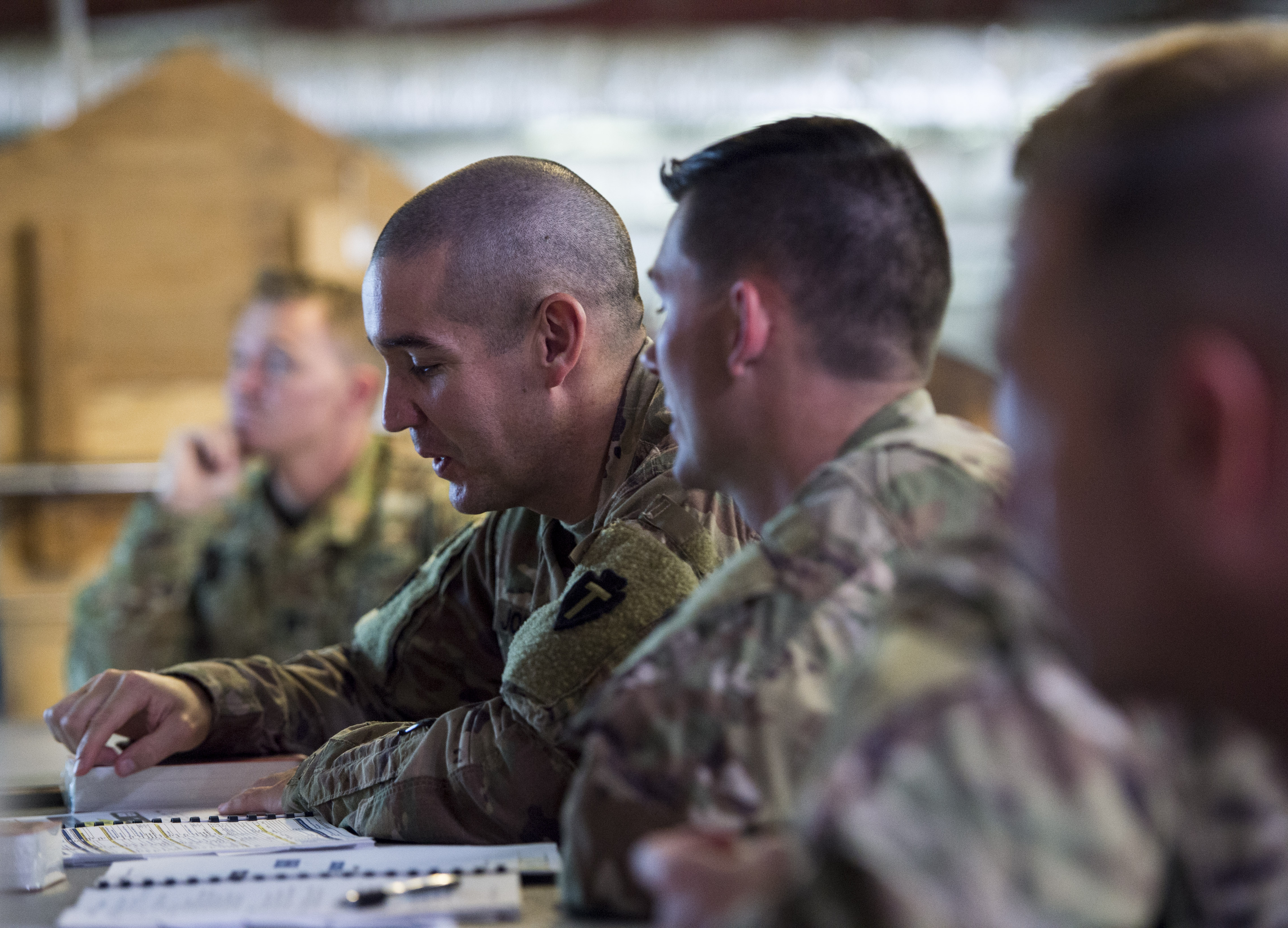 U.S. service members assigned to Combined Joint Task Force - Horn of Africa discuss a plan for military involvement in a simulated disaster relief operation during a U.S. Agency for International Development's Joint Humanitarian Operations Course at Camp Lemonnier, Djibouti, March 9, 2018. Members attended the second two-day course, which highlighted international disaster response, best practices, and the U.S. military's role when supporting humanitarian assistance and disaster relief operations. (U.S. Air Force photo by Staff Sgt. Timothy Moore)