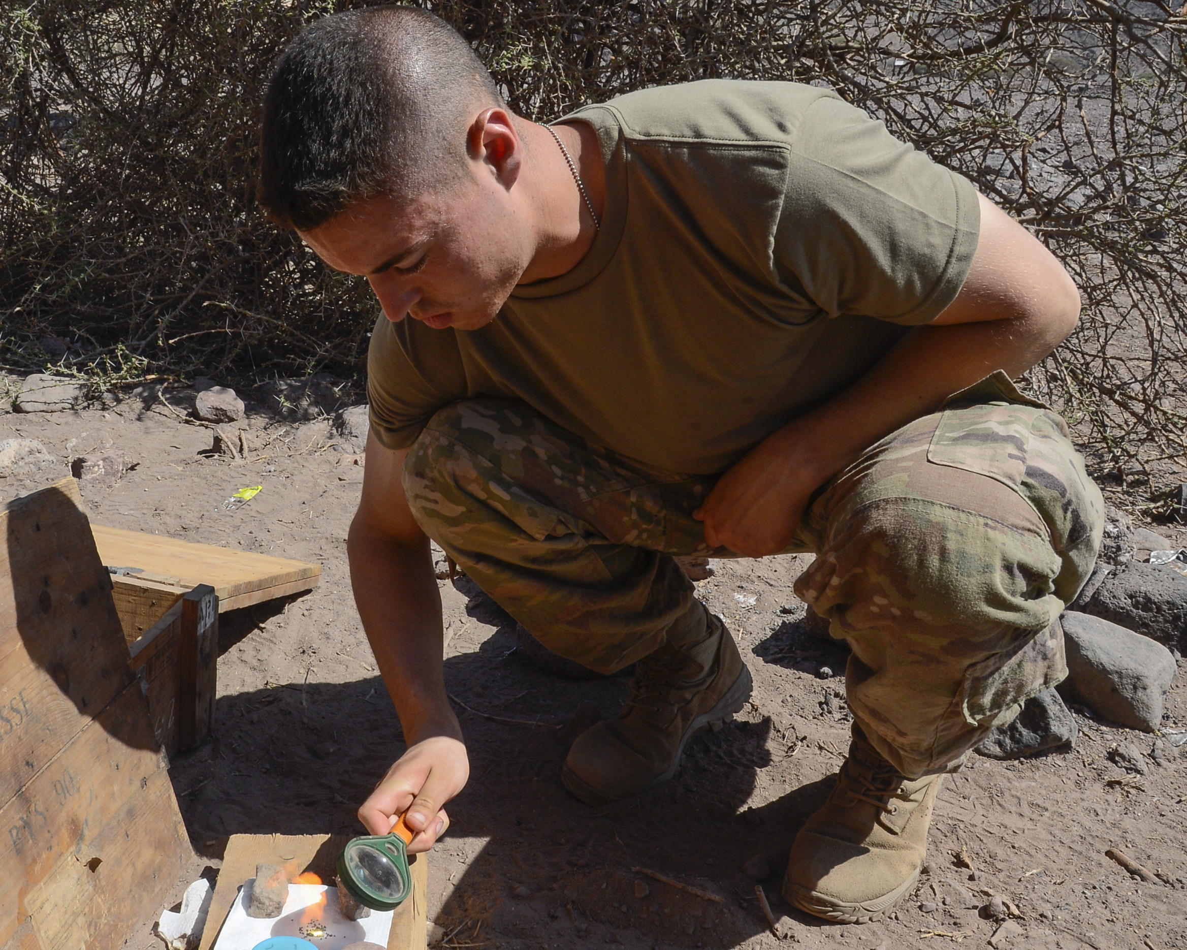 U.S. Army Pfc. Derek Gauss assigned to Alpha Company, 1st Battalion, 32nd Infantry Regiment, 1st Brigade Combat Team, 10th Mountain Division, lights a fire with a magnifying glass as part of a desert survival class during the French Desert Commando Course at the Centre Dentrainment Au Combat Djibouti in Arta Plage, Djibouti, April 21, 2018. The four-day phase is the first of two necessary to earn a coveted French Desert Commando Badge. (U.S. Navy Photo by Mass Communication Specialist 2nd Class Timothy M. Ahearn)