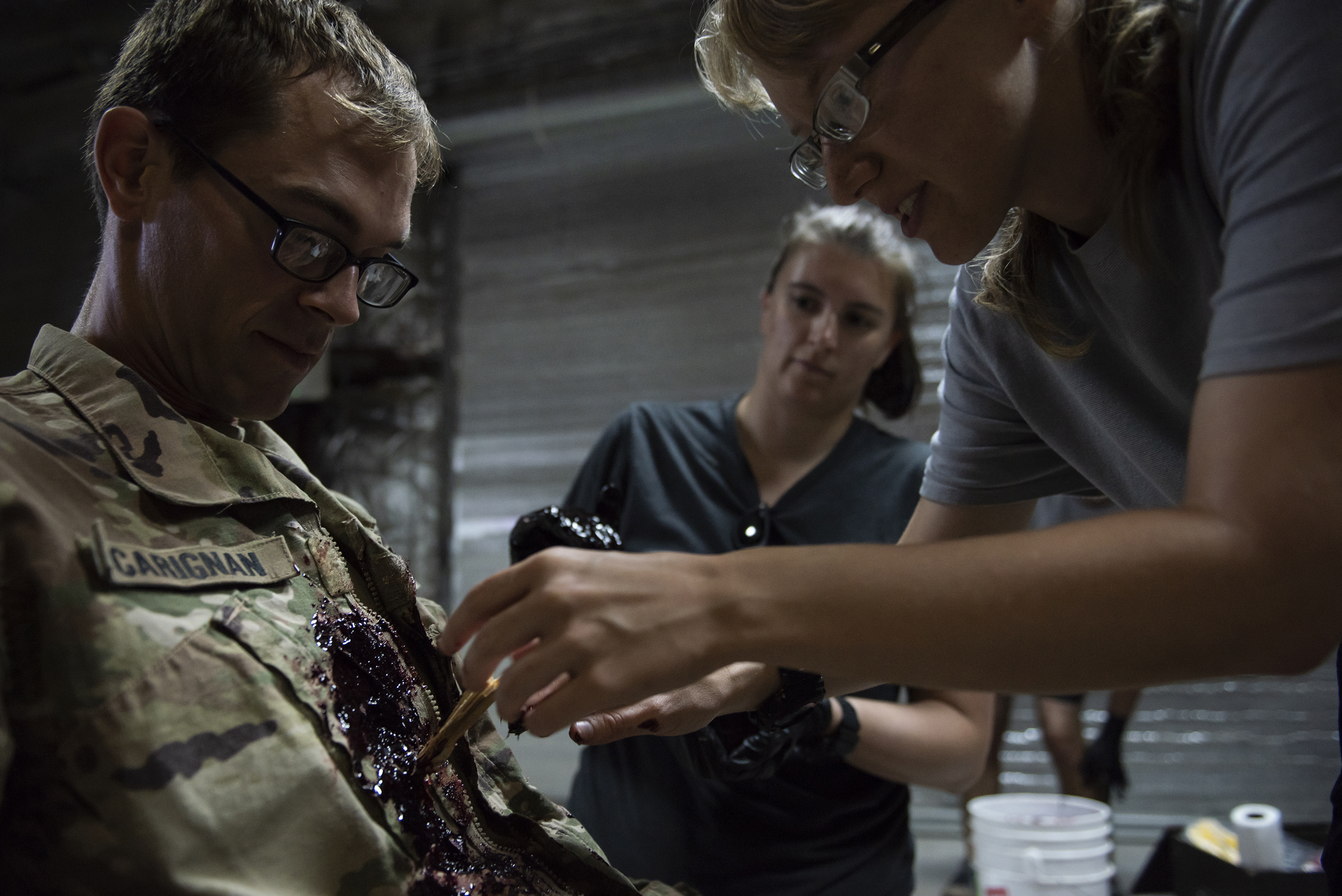 U.S. Air Force Senior Airman Emily Baker, a medical material specialist in the 82nd Expeditionary Rescue Squadron, moulages a simulated chest injury on U.S. Army Sgt. Ryan Carignan, Surgeon Cell, Combined Joint Task Force - Horn of Africa, on Camp Lemonnier, Djibouti, April 24, 2018. As part of a joint mass-casualty training exercise, service members performed various tasks in order to locate, secure and rescue simulated casualties. (U.S. Air National Guard photo by Master Sgt. Sarah Mattison)