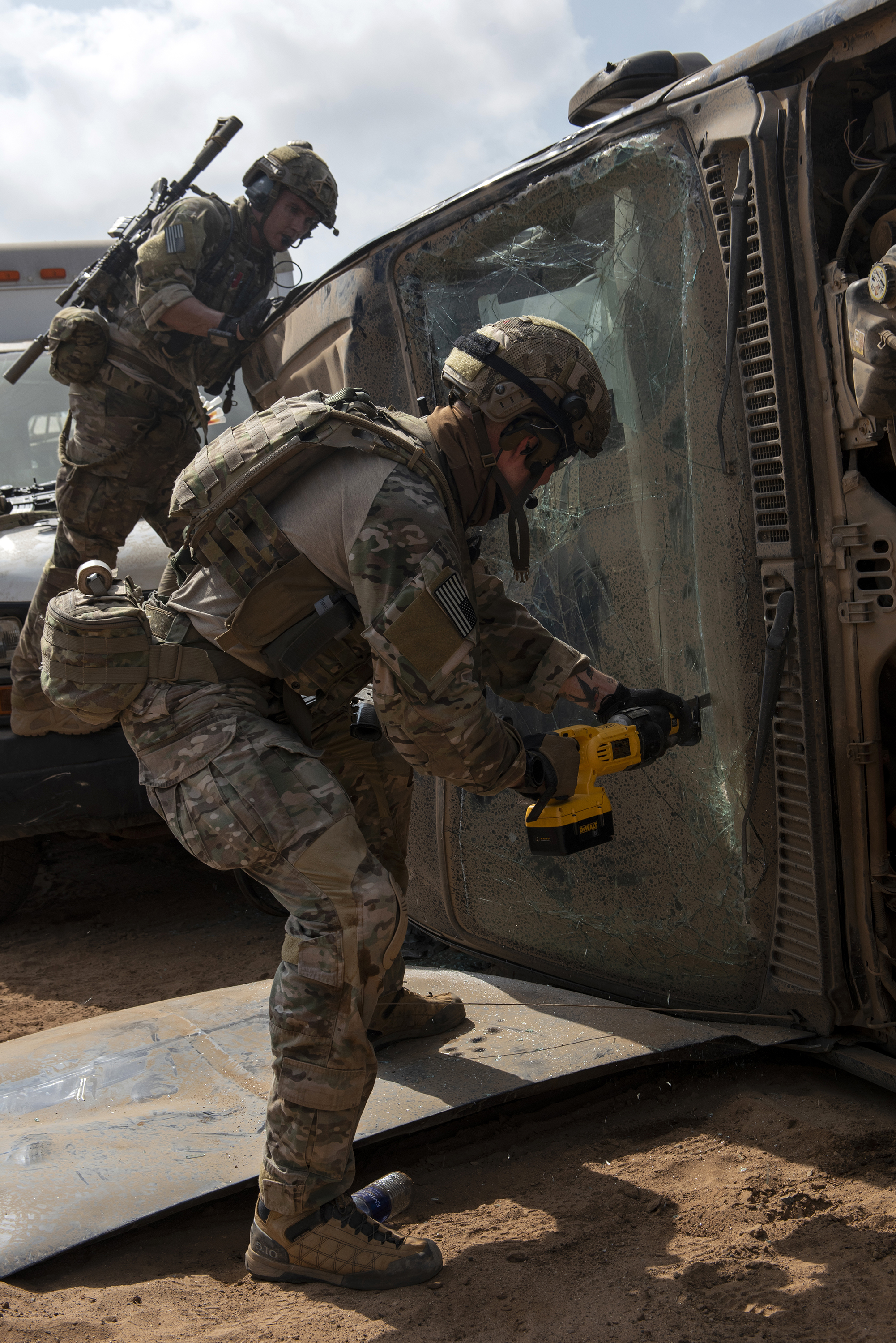 A Pararescueman from the 82nd Expeditionary Rescue Squadron, cuts through the windshield of an overturned vehicle in order to rescue a simulated casualty in Djibouti City, Djibouti, April 24, 2018. The Airmen conducted various extrication techniques during a joint mass casualty training exercise. (U.S. Air National Guard photo by Master Sgt. Sarah Mattison)