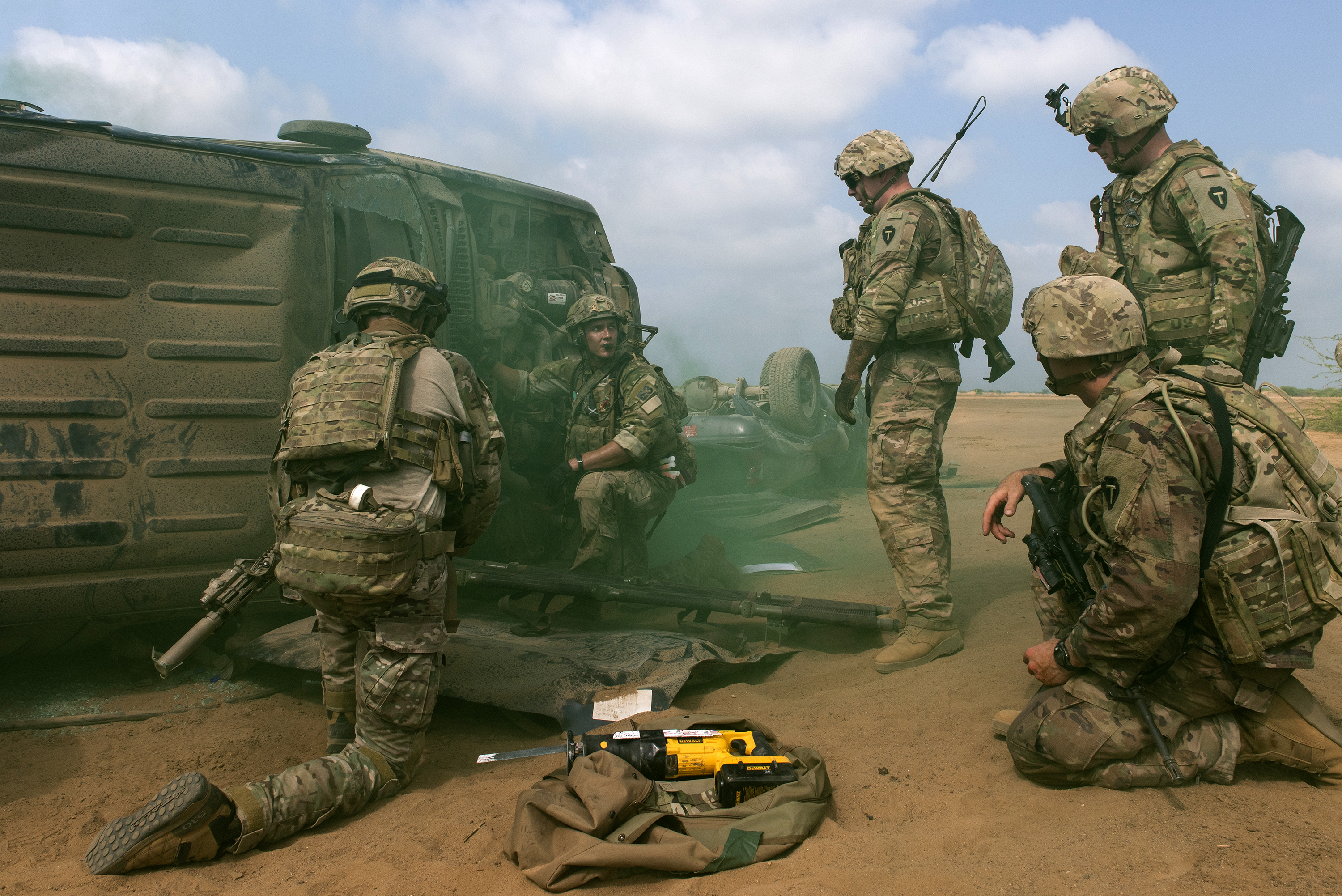 U.S. Air Force Pararescuemen from the 82nd Expeditionary Rescue Squadron and U.S. Soldiers with 3rd Battalion, 144th Infantry Regiment, Texas Army National Guard, prepare to move a simulated casualty onto a litter in Djibouti City, Djibouti, April 24, 2018. As part of a joint mass-casualty training exercise, service members performed various tasks in order to locate, secure and rescue simulated casualties. (U.S. Air National Guard photo by Master Sgt. Sarah Mattison) (Portions of this image were obscured for security reasons)