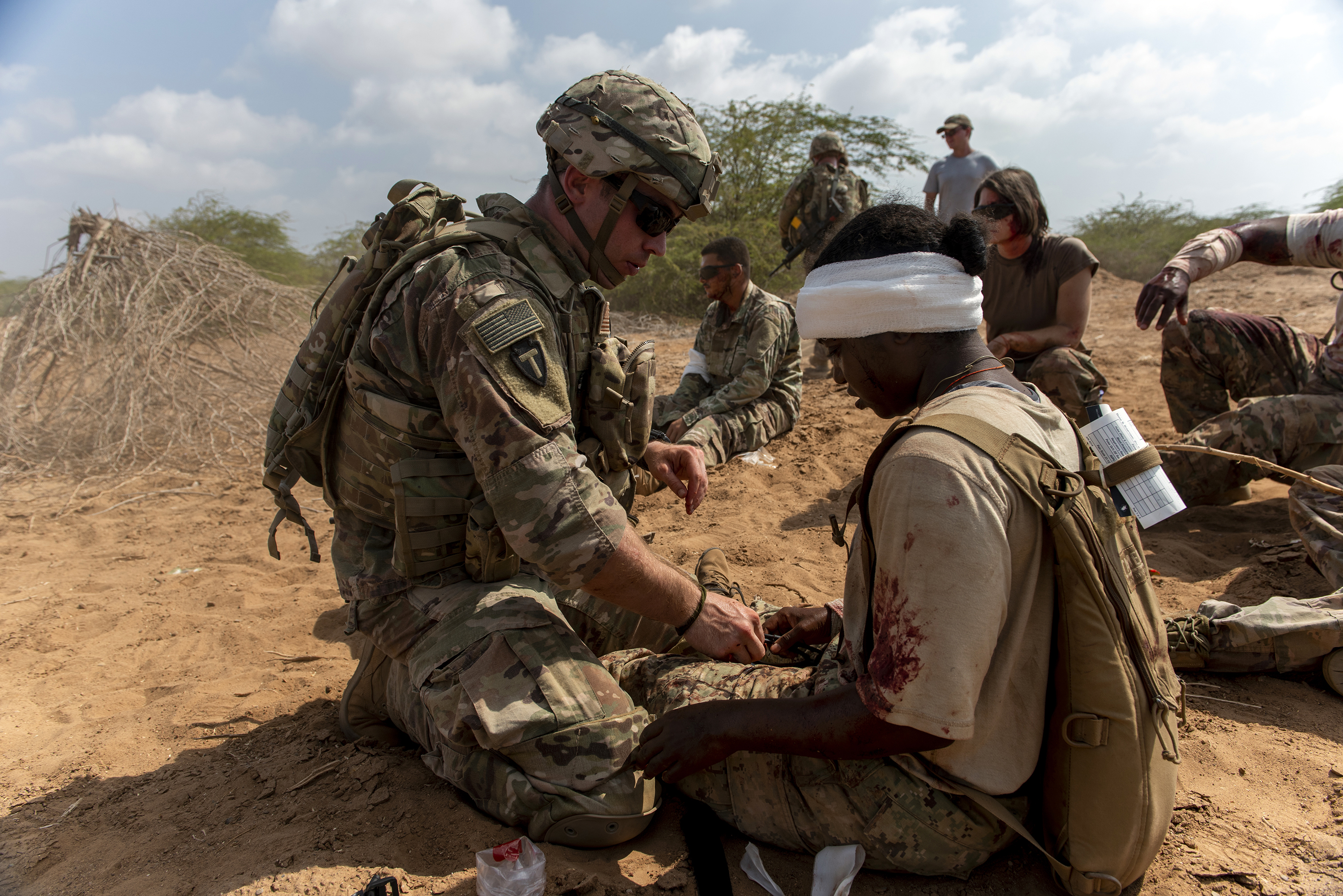 A Guardsman with the 3rd Battalion, 144th Infantry Regiment, Texas Army National Guard, treats a simulated casualty in Djibouti City, Djibouti, April 24, 2018. As part of a joint mass casualty training exercise, service members performed various tasks in order to locate, secure and rescue simulated casualties. (U.S. Air National Guard photo by Master Sgt. Sarah Mattison)