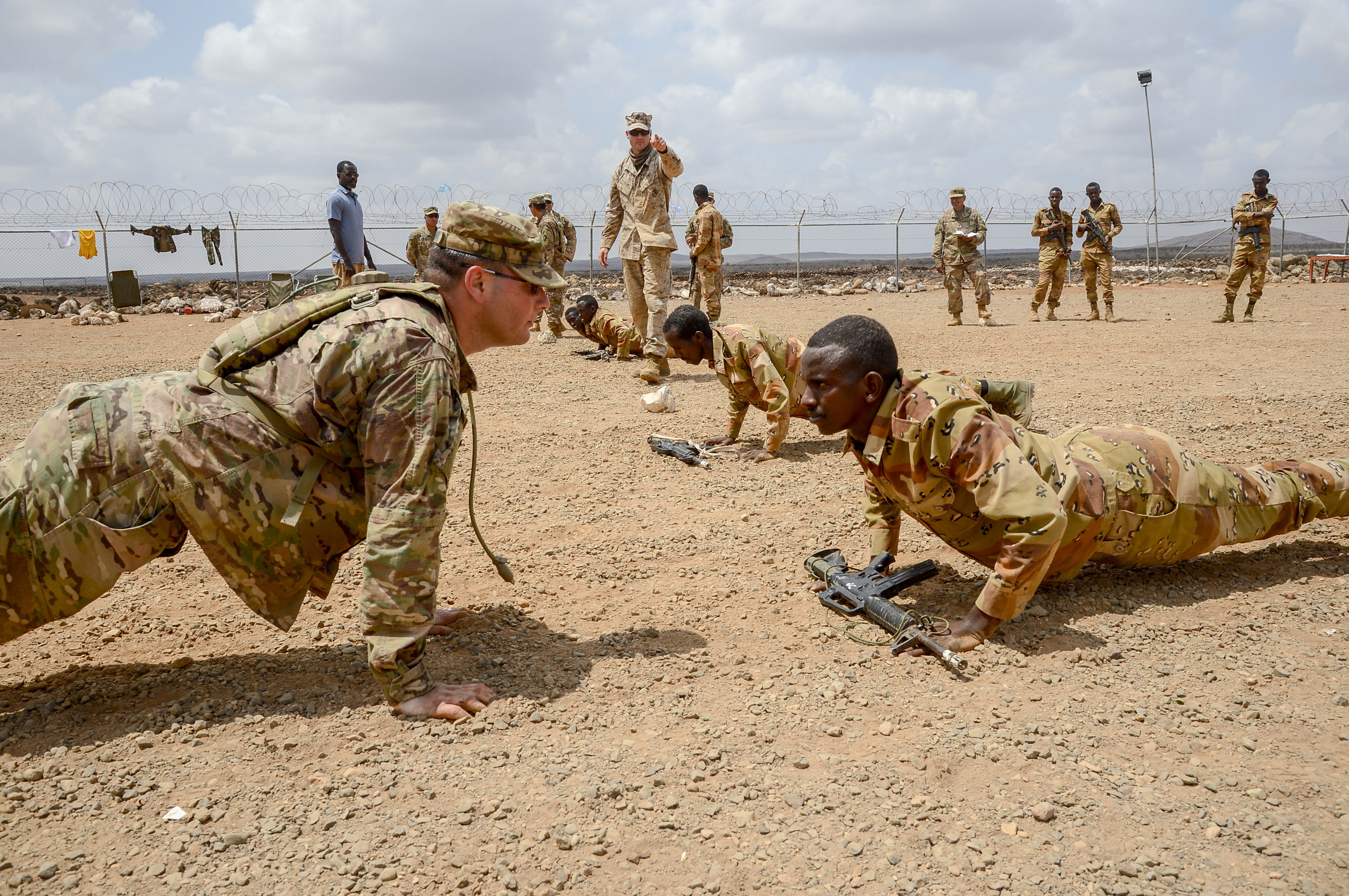 U.S. Army Sergeant Vincent Merriman, Alpha Company, 3rd Battalion, 141st Infantry Regiment, Texas National Guard, demonstrates a proper pushup for a Djiboutian soldier at a training site outside Djibouti City, April 19, 2018. U.S. service members have been training the Djiboutian Army's Rapid Intervention Battalion, a newly formed crisis response unit. (U.S. Navy Photo by Mass Communication Specialist 2nd Class Timothy M. Ahearn)