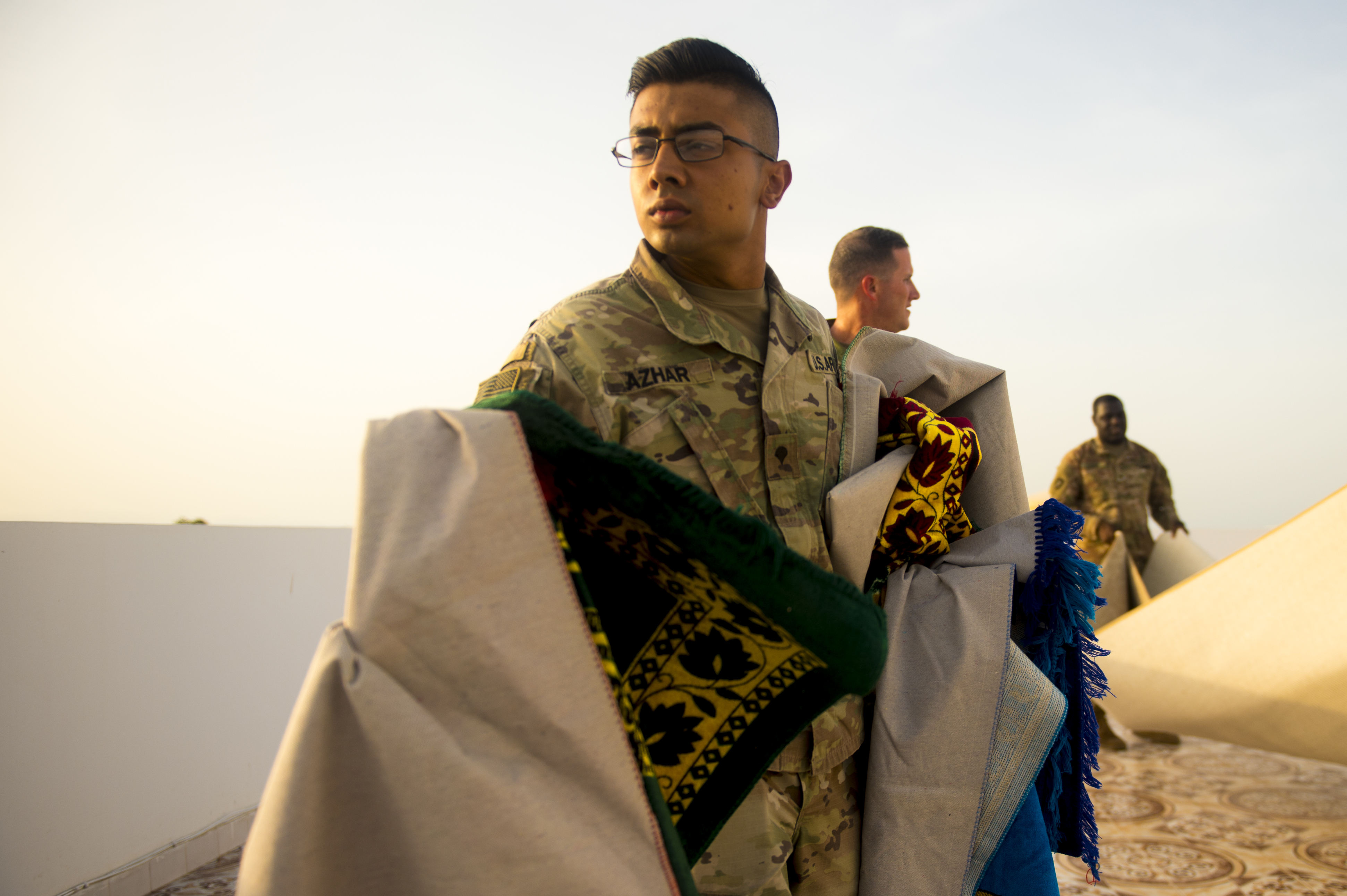 U.S. Army Spc. Ahmed Azhar, an infantryman from the 10th Mountain Division, prepares a prayer rug in during an Iftar celebration at the U.S. Ambassador to the Republic of DJibouti's house in Djibouti, May 21, 2018. The U.S. Ambassador to the Republic of Djibouti, Larry André, opened his home to celebrate two Iftars, one run by the Defense Attaché Office for senior Diboutian Military and security leaders, the second for senior government, diplomatic, and business leaders. (U.S. Air Force photo by Senior Airman Scott Jackson)