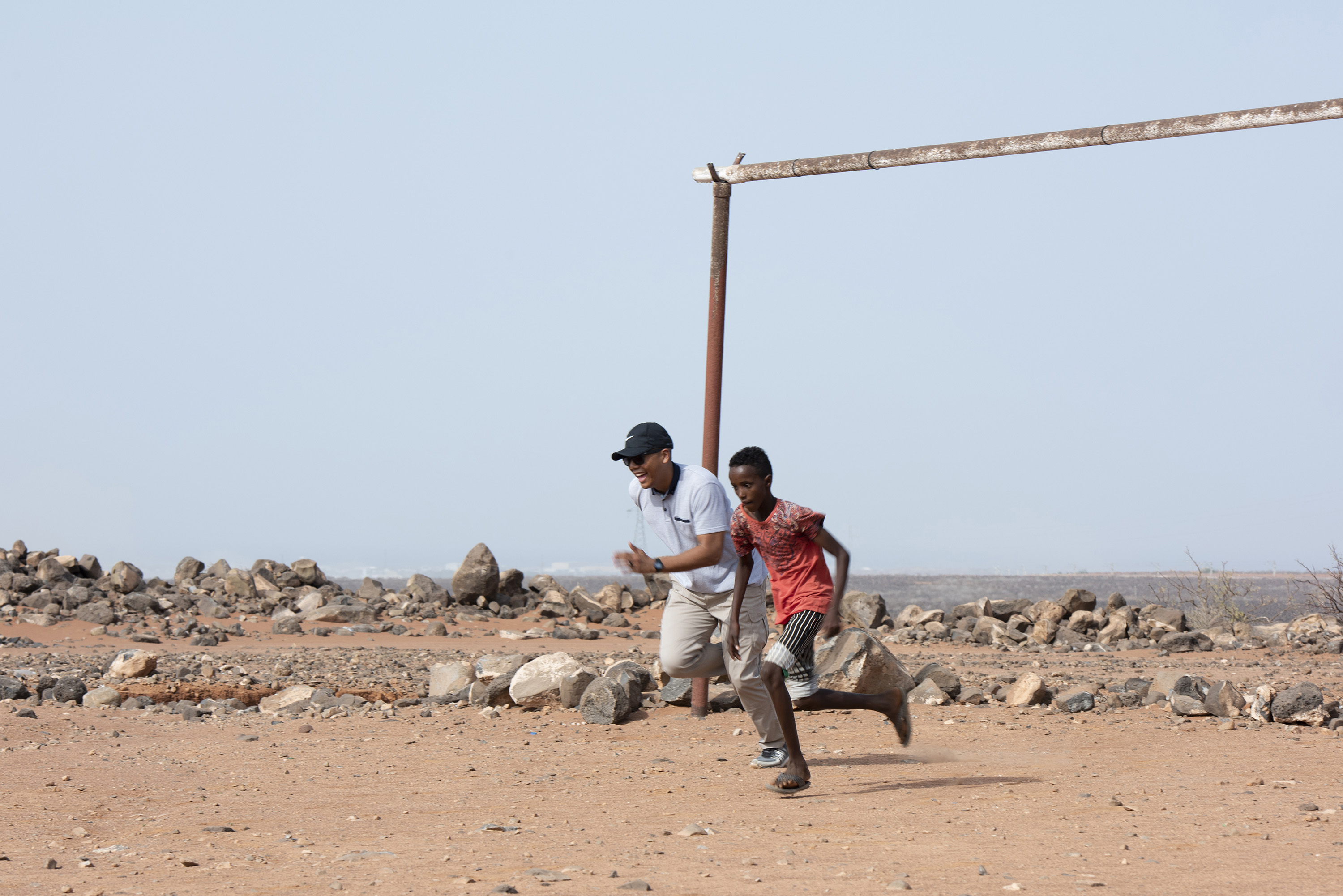 U.S. Air Force 1st Lt. Darren Domingo, officer in charge, Combat Camera, assigned to Combined Joint Task Force - Horn of Africa, races with a child from the local village outside of Chebelley Village, Djibouti, Aug. 3, 2018. Domingo was one of 30 service members participating in an outreach event organized by the 404th Civil Affairs Battalion. (U.S. Air National Guard photo by Master Sgt. Sarah Mattison)