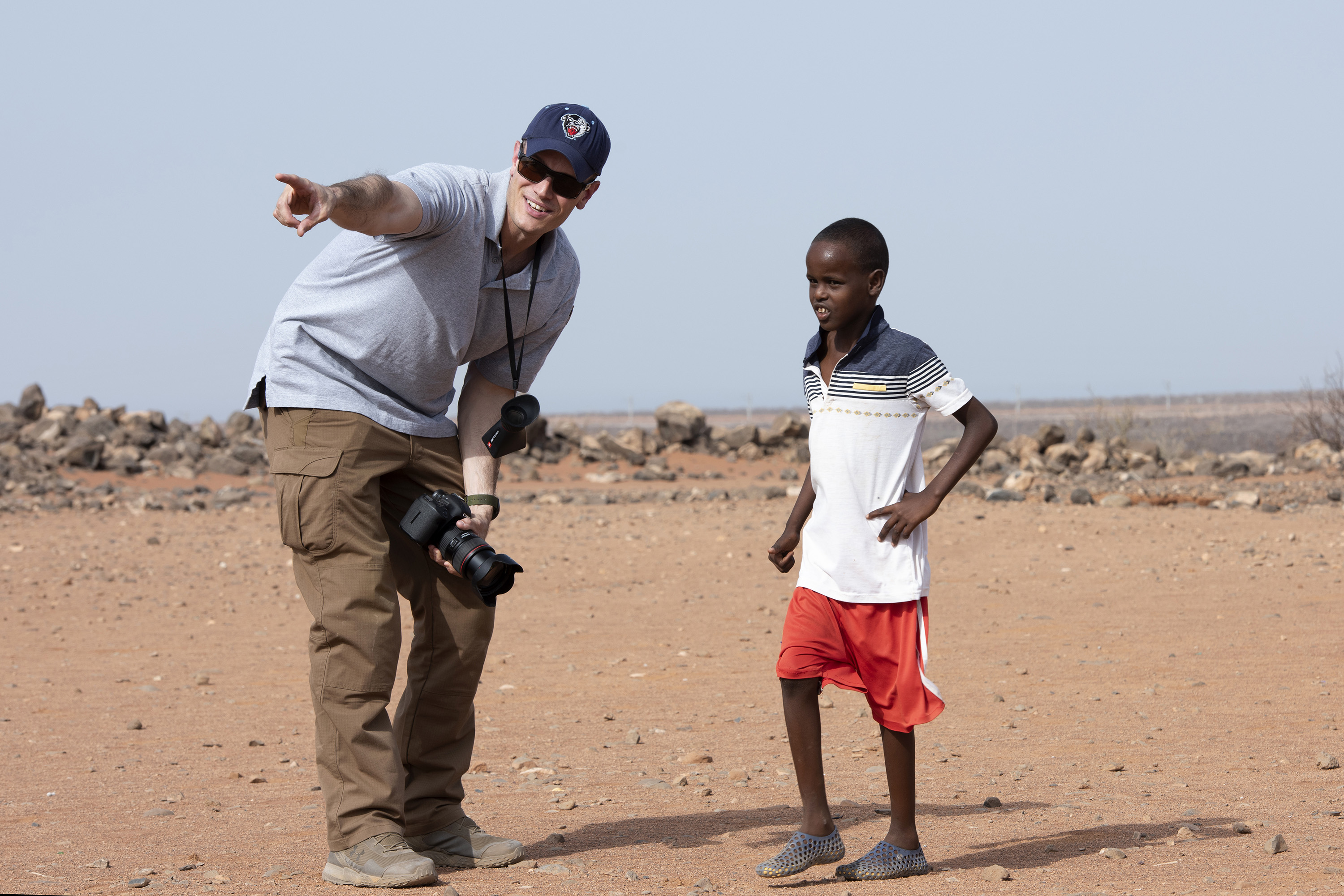 U.S. Air Force Master Sgt. Andrew Sinclair, broadcaster, Combined Joint Task Force - Horn of Africa, public affairs, speaks with a Djiboutian child outside of Chebelley village, Djibouti, Aug. 3, 2018. Sinclair was there to document a soccer game as part of a community engagement event organized by the 404th Civil Affairs Battalion. (U.S. Air National Guard photo by Master Sgt. Sarah Mattison)