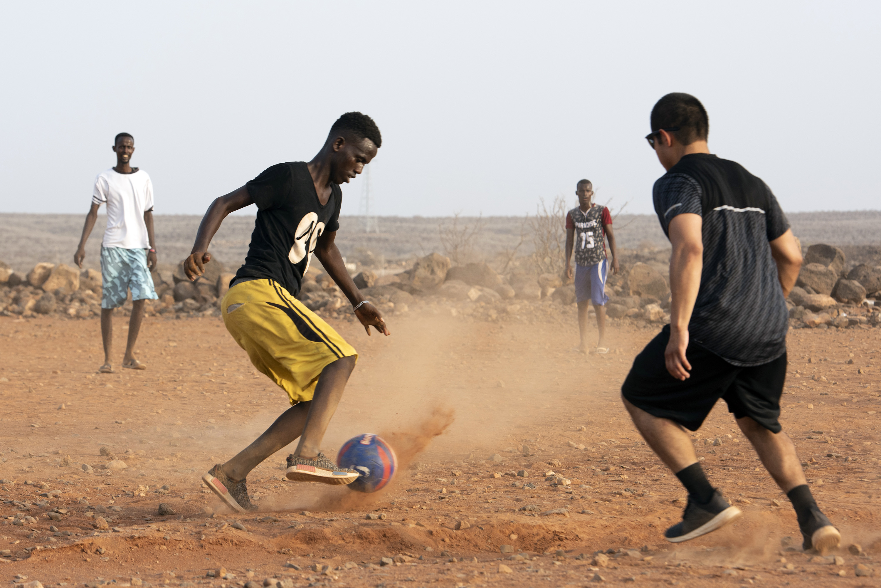 U.S. Service members assigned to Combined Joint Task Force - Horn of Africa participate in a friendly game of soccer with children from the nearby village, outside of Chebelley village, Djibouti, Aug. 3, 2018. Over 30 Soldiers and Airmen volunteered for the outreach event organized by the 404th Civil Affairs Battalion. (U.S. Air National Guard photo by Master Sgt. Sarah Mattison)