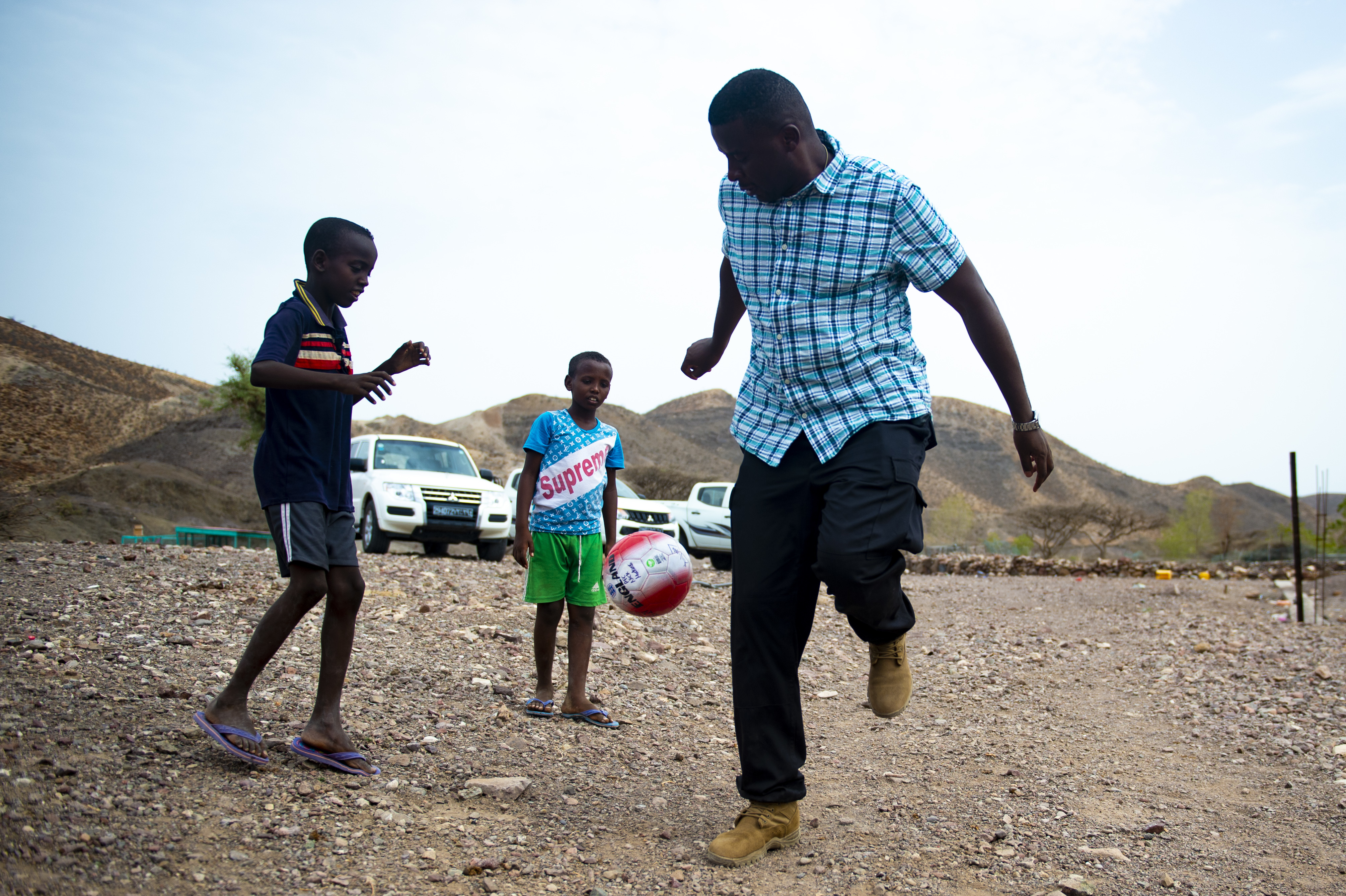 Spc. Apollo Luanje, 404th Civil Affairs Battalion, plays soccer with children in the village Ribta in the Tadjoura region of Djibouti, August 15, 2018. 407th Civil Affairs mission is to develop and maintain relationships with communities. (U.S. Air Force photo by Senior Airman Scott Jackson)