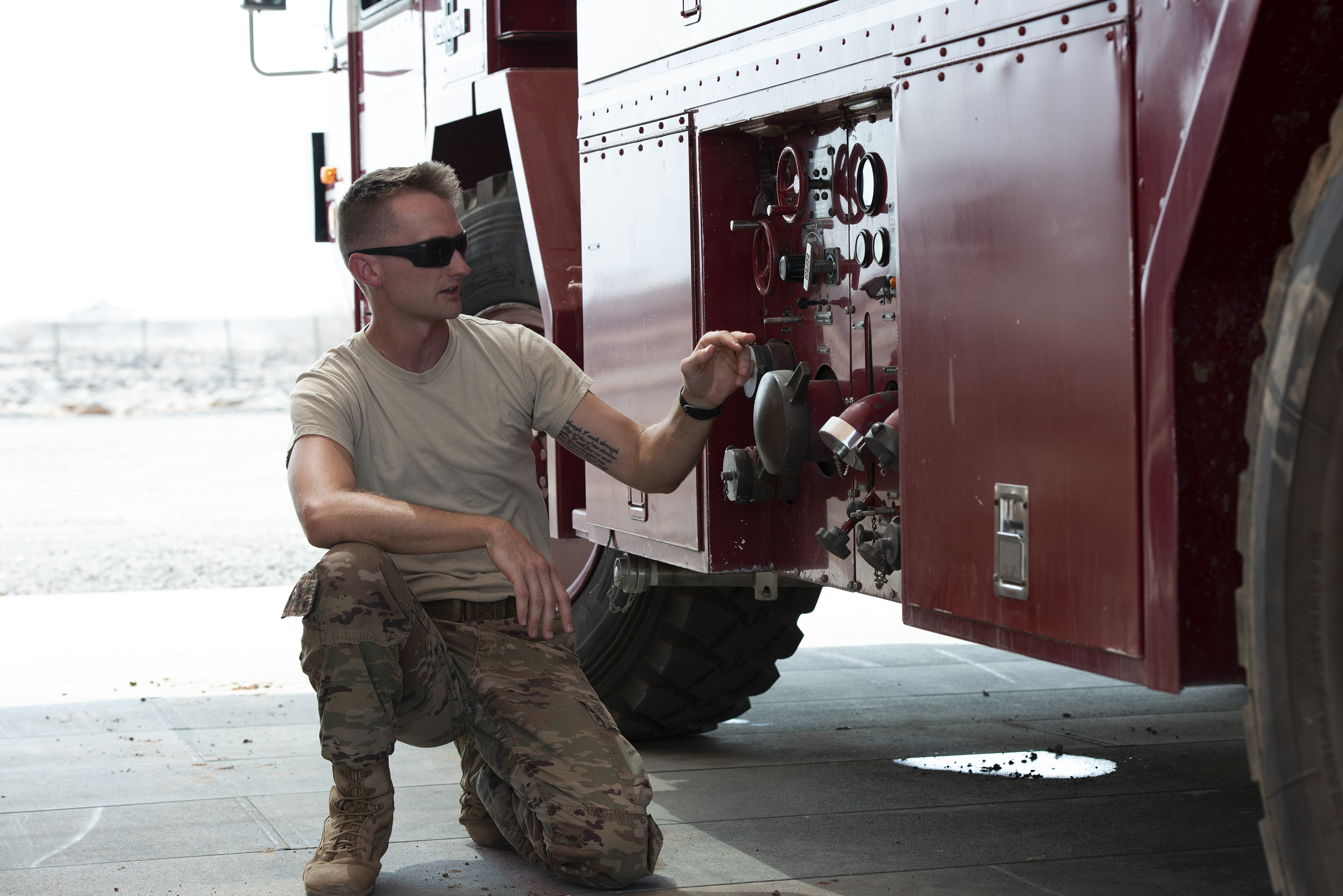 An Airman from the 870th Air Expeditionary Squadron's fire department, 449th Air Expeditionary Group, describes the functions of one of the control panels on a P-19B fire truck, outside Djibouti City, Djibouti, Aug. 20, 2018. The fire fighters continually perform scenario based training in order to maintain their skills. (U.S. Air National Guard photo by Master Sgt. Sarah Mattison)