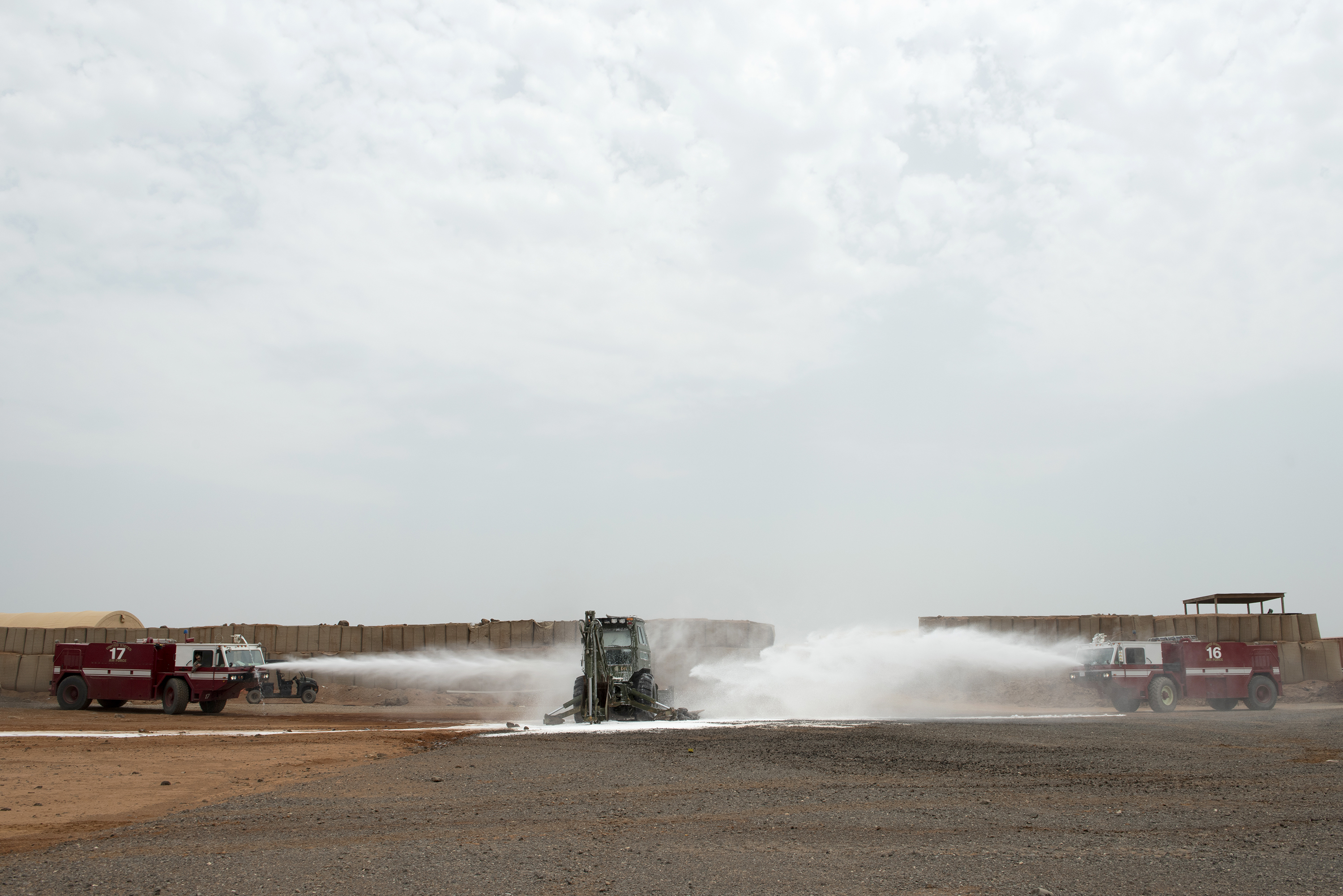 U.S. Air Force firefighters with the 449th Air Expeditionary Group and Combined Joint Task Force Horn of Africa use a P-19B fire truck to fight a simulated fire during training, outside Djibouti City, Djibouti, Aug. 20, 2018. The Airmen continually perform scenario based training tasks in order to maintain their skills. (U.S. Air National Guard photo by Master Sgt. Sarah Mattison) (A portion of the background was blurred for security purposes)