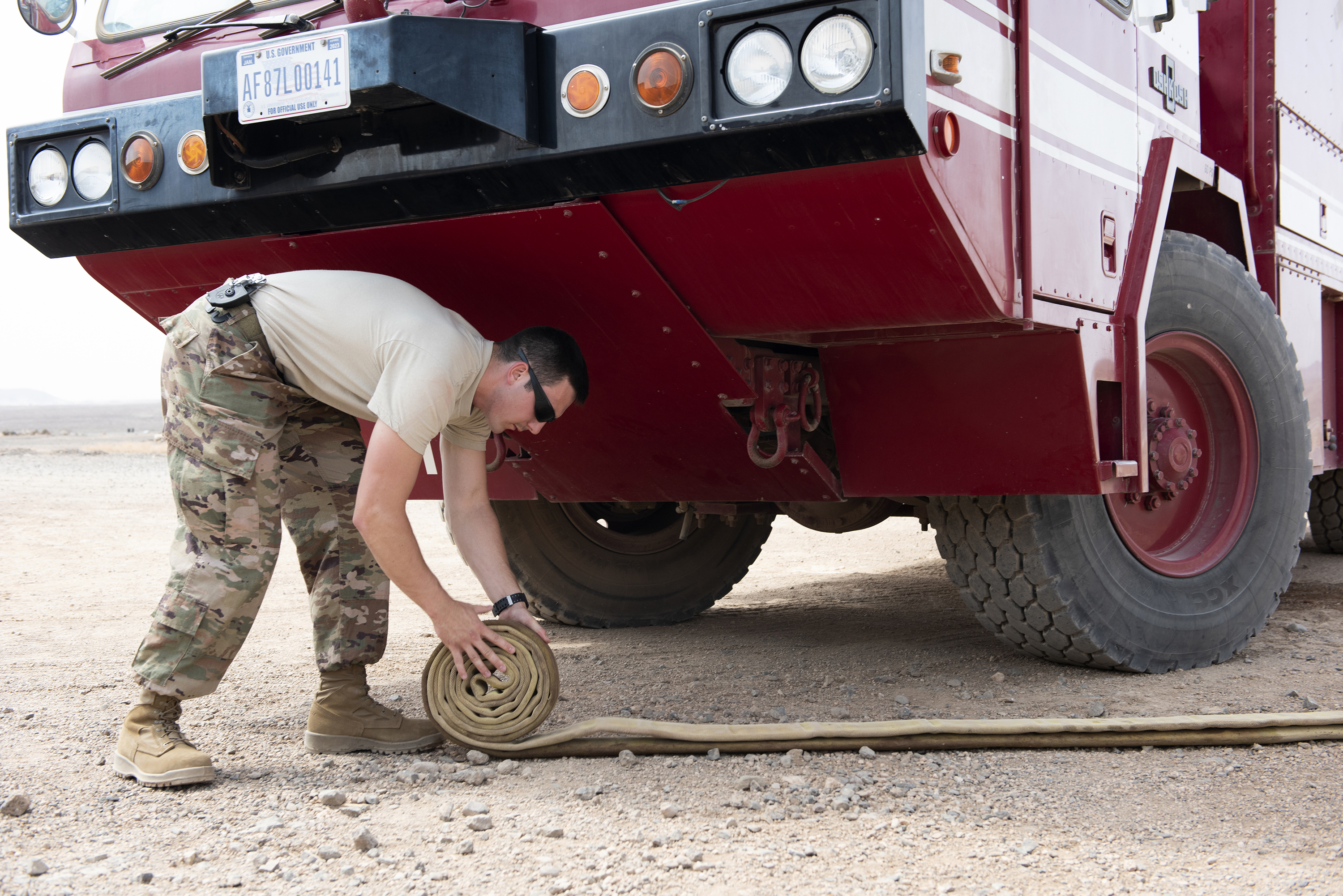 An Airman assigned to Combined Joint Task Force - Horn of Africa, rolls up a fire hose after filling the tank on a P-19B fire truck, outside Djibouti City, Djibouti, Aug. 20, 2018. The Airmen preform daily inspections on their trucks and equipment in order to maintain readiness. (U.S. Air National Guard photo by Master Sgt. Sarah Mattison)