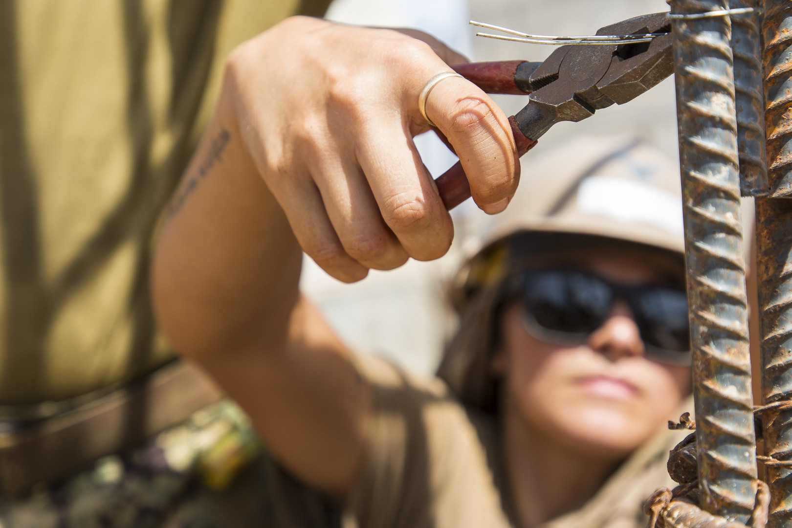 U.S. Navy Construction Electrician 3rd Class Sandra Elly, a Seabee assigned to Naval Mobile Construction Battalion 1 (NMCB 1) ties in rebar at a construction site in Ali Oune, Djibouti, Sept.19, 2018. Seabees from NMCB 1 Detachment Horn of Africa are building a medical facility in Ali Oune in support of the Ministry of Health for Djibouti. (U.S. Air National Guard photo by Master Sgt. Andrew Sinclair)