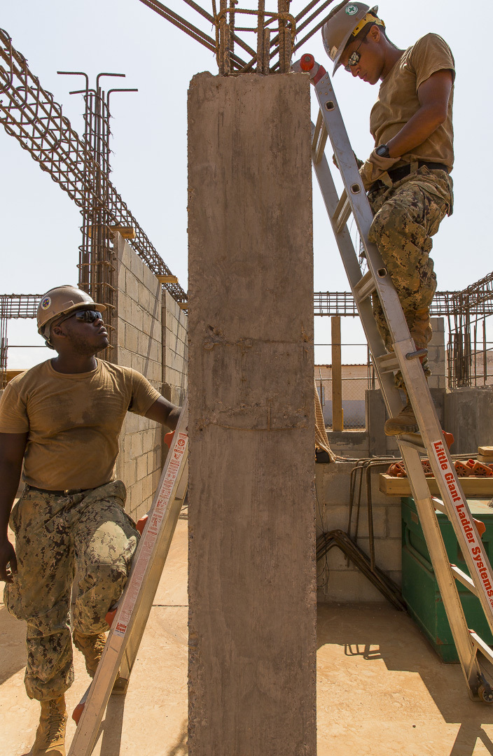 U.S. Navy Engineering Aid 3rd Class Tabari Fells spots Steelworker 2nd Class Timothy Vincent, Seabees assigned to Naval Mobile Construction Battalion 1, Detachment-Horn of Africa (NMCB 1, Det-HOA) as part of routine safety at a construction site in Ali Oune, Djibouti, Sept. 19, 2018. Seabees from NMCB 1, Det-HOA are building a medical facility in Ali Oune in support of the Ministry of Health for Djibouti. (U.S. Air National Guard photo by Master Sgt. Andrew Sinclair)