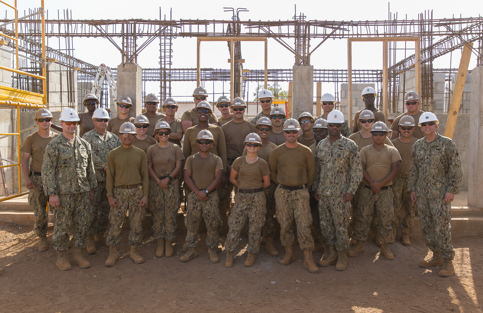 U.S. Navy Seabees with Naval Mobile Construction Battalion 1, Detachment Horn of Africa (NMCB 1, Det-HOA) stop for a photo with NMCB-1's Civil Engineer Corps Cmdr. Michael Meno and Command Master Chief Derrick Arrington at a project site in Ali Oune, Djibouti, Sept.19, 2018. NMCB-1, Det-HOA is building a medical facility in Ali Oune in support of the Ministry of Health for Djibouti. (U.S. Air National Guard photo by Master Sgt. Andrew Sinclair)