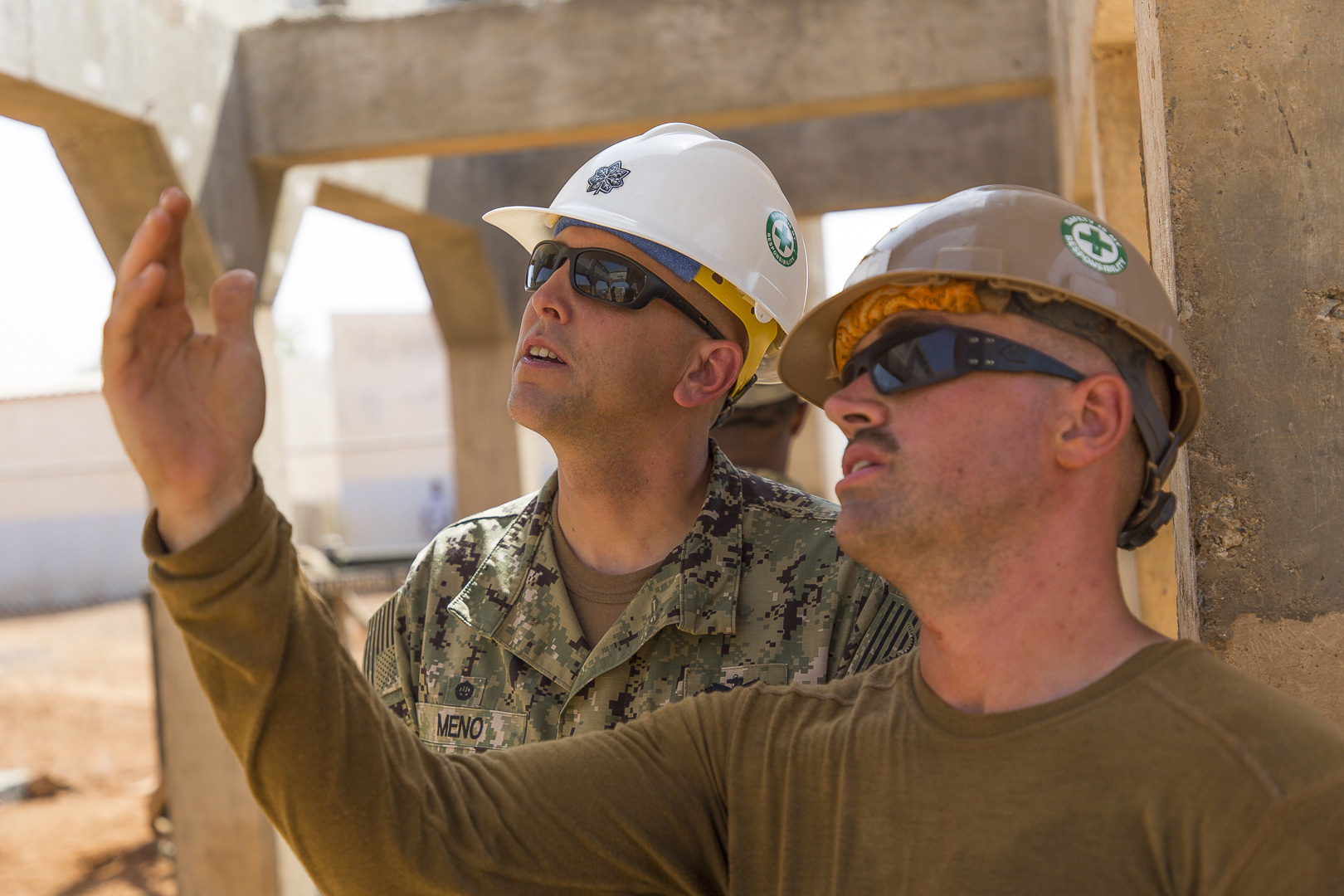 U.S. Navy Builder 2nd Class Erik Rau a Seabee assigned to Naval Mobile Construction Battalion 1, Detachment-Horn of Africa (NMCB 1 Det-HOA), gives Civil Engineer Corps Cmdr. Michael Meno a tour of the construction site in Ali Oune, Djibouti, Sept. 19, 2018. Seabees with NMCB 1 Det-HOA are building a medical facility in Ali Oune in support of the Ministry of Health for Djibouti. (U.S. Air National Guard photo by Master Sgt. Andrew Sinclair)