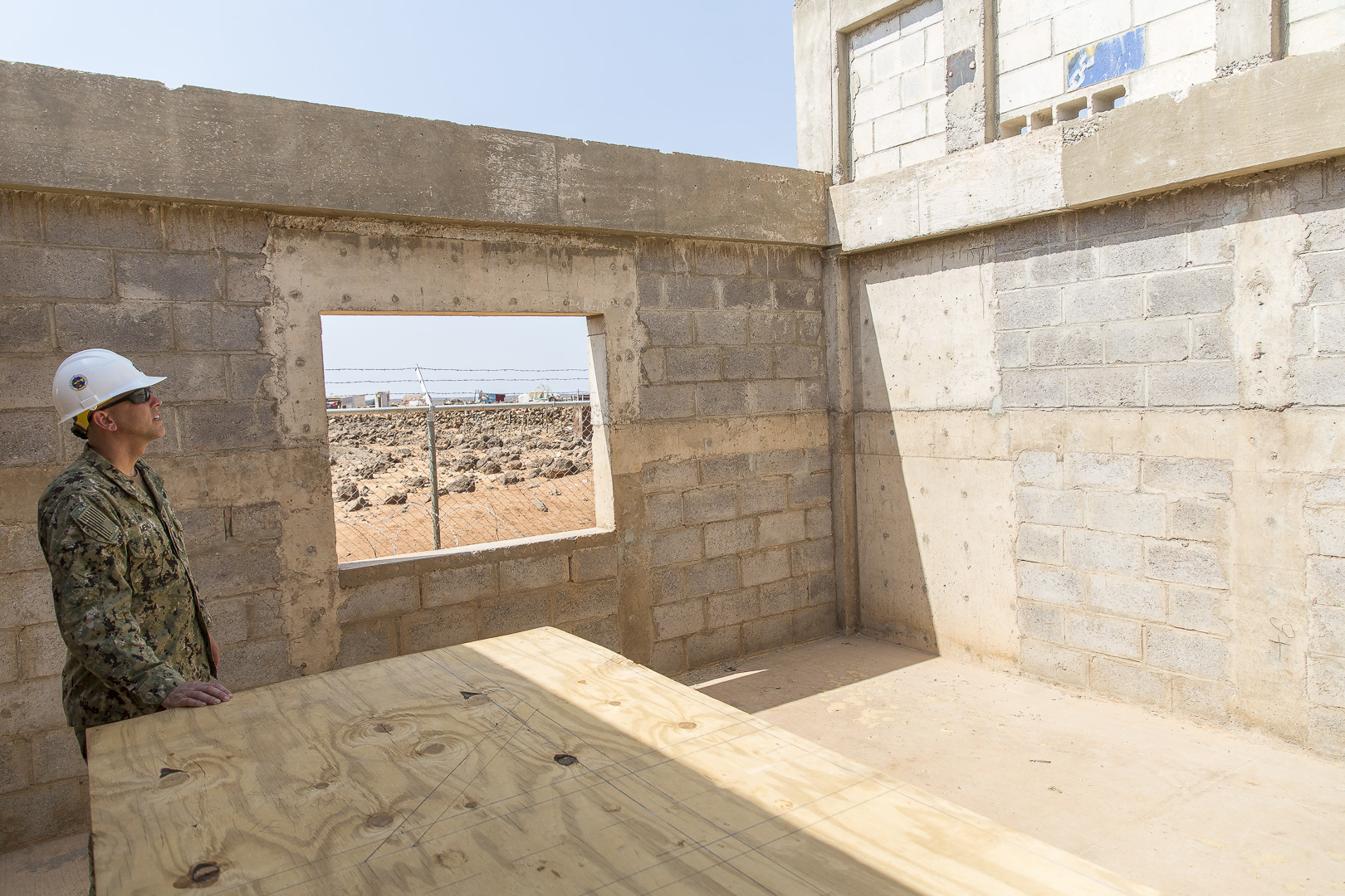 U.S. Navy Civil Engineer Corp Cmdr. Michael Meno, Naval Mobile Construction Battalion 1 commander, observes construction of a nursery in Ali Oune, Djibouti, Sept. 19, 2018. Seabees with NMCB 1, Detachment-Horn of Africa are building a medical facility in Ali Oune in support of the Ministry of Health for Djibouti. (U.S. Air National Guard photo by Master Sgt. Andrew Sinclair)