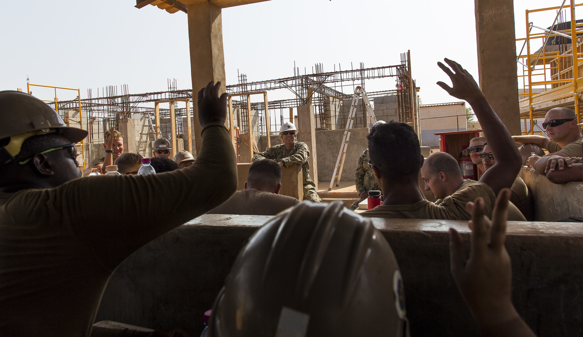 U.S Navy Civil Engineer Corps Cmdr. Michael Meno, Naval Mobile Construction Battalion 1 (NMCB 1) commander, answers questions from Seabees assigned to a construction site in Ali Oune, Djibouti, Sept. 19, 2018. Seabees with NMCB 1 Detachment Horn of Africa are building a medical facility in Ali Oune in support of the Ministry of Health for Djibouti. (U.S. Air National Guard photo by Master Sgt. Andrew Sinclair)
