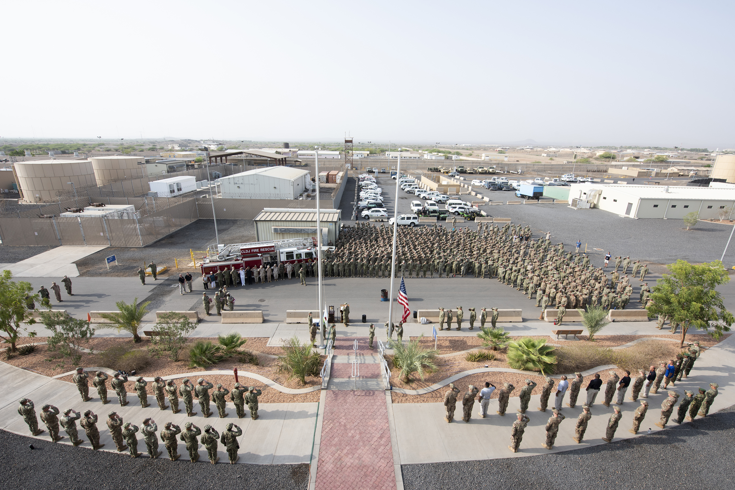 U.S. service members salute as the American and Djiboutian flags are raised on Camp Lemonnier, Djibouti, Sept. 11, 2018. The service members were gathered for a 9/11 remembrance ceremony to recognize those who lost their lives 17 years ago. (U.S. Air National Guard photo by Master Sgt. Sarah Mattison)