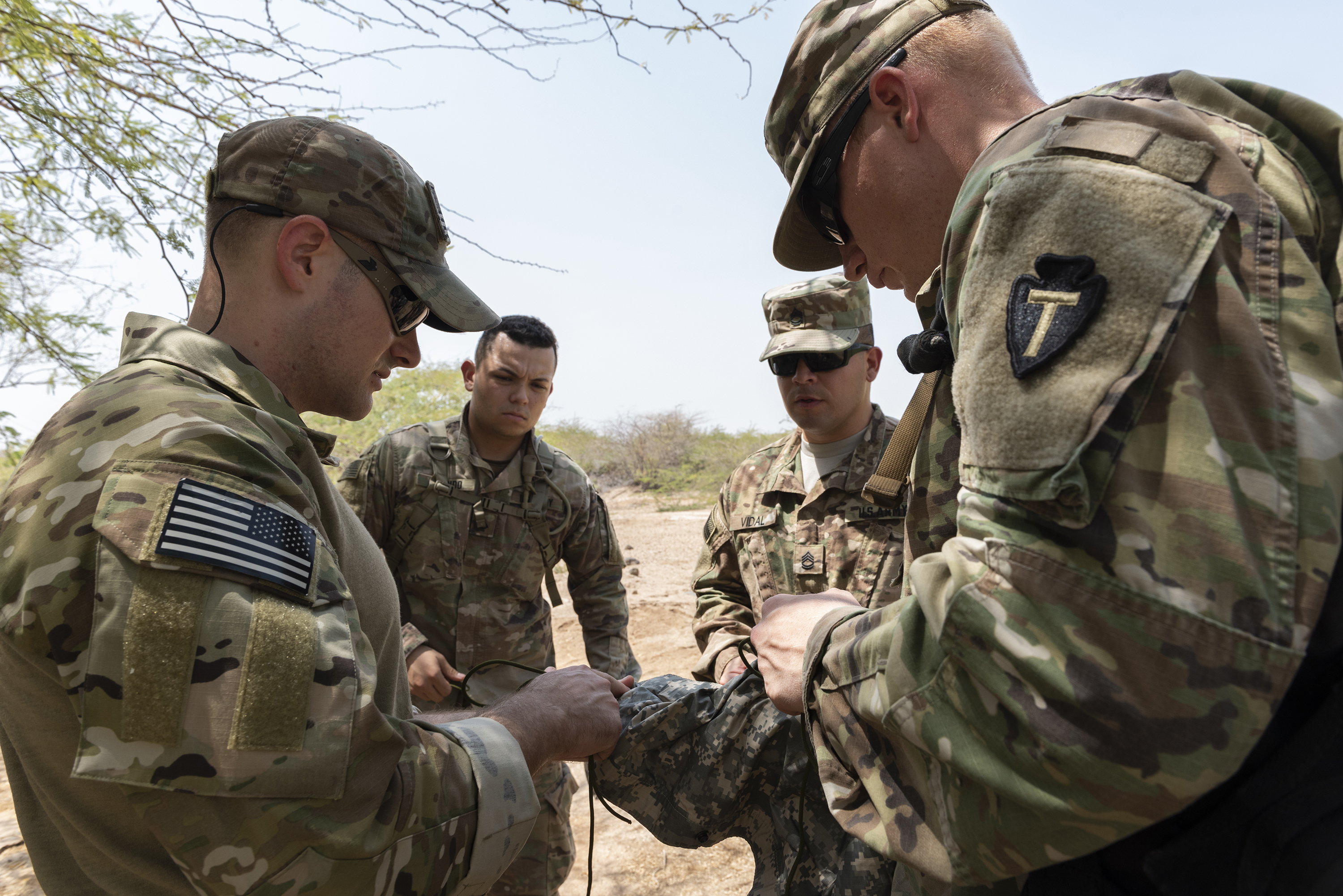 From Left: U.S. Air Force Tech. Sgt. Adam Murphy, a survival, evasion, resistance and escape specialist assigned to Combined Joint Task Force-Horn of Africa, teaches U.S. Army Pfc. Jonathan Galindo, a field artillery firefinder radar operator, Sgt. 1st Class Amando Vidal, a field artillery firefinder radar operator, and Spec. Killian Tooke, a radar repairer, all assigned to 3rd Battalion, 133rd Field Artillery Regiment, Texas National Guard, how to create a slipknot, bowline and a trucker's hitch during survival skills training on Camp Lemonnier, Djibouti, Oct. 13, 2018. During this training, service members performed various skills such as constructing a shelter, finding alternative water sources and signaling for rescue. (U.S. Air National Guard photo by Master Sgt. Sarah Mattison)