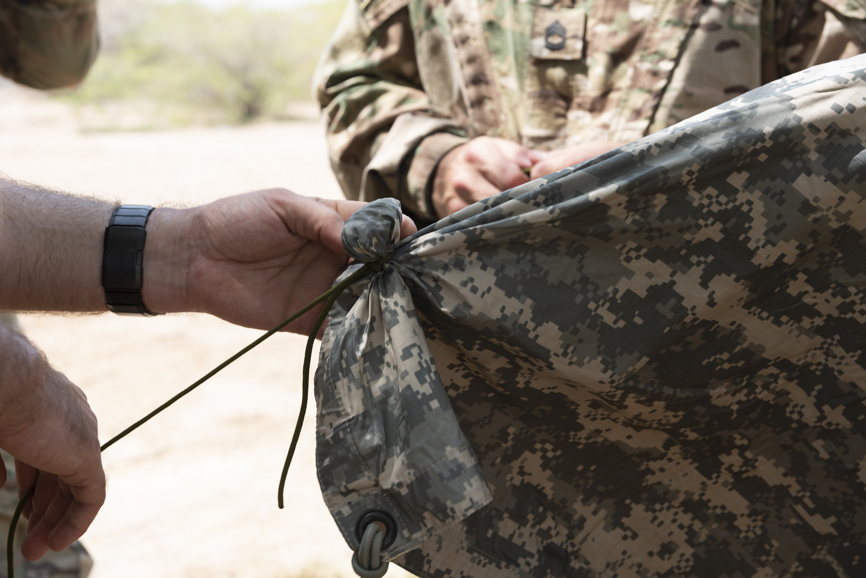 U.S. Air Force Tech. Sgt. Adam Murphy, a survival, evasion, resistance and escape specialist assigned to Combined Joint Task Force-Horn of Africa, demonstrates how to create a button on a poncho liner during survival skills training on Camp Lemonnier, Djibouti, Oct. 13, 2018. During this training, service members performed various skills such as constructing a shelter, finding alternative water sources and signaling for rescue. (U.S. Air National Guard photo by Master Sgt. Sarah Mattison)