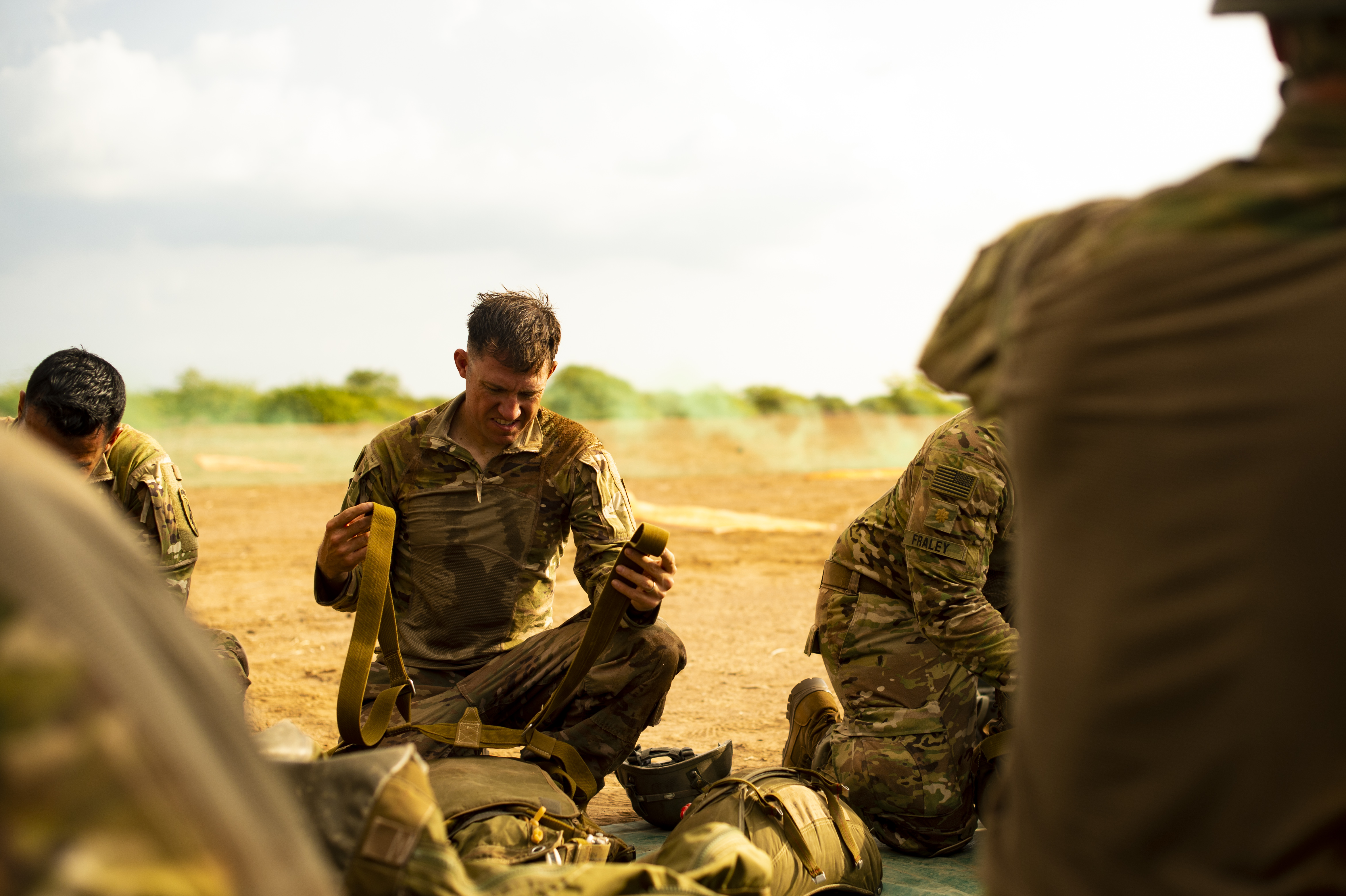 U.S. Army Capt. Mark Olving, team leader, Civil Affairs Team 305, 404th Civil Affairs battalion, packs his parachute bag after a static line jump outside Djibouti City, Djibouti, Oct. 1, 2018. American servicemembers and coalition partners jumped together to celebrate the Feast Day of Archangel Michael, the patron saint of paratroopers. (U.S. Air Force photo by Senior Airman Scott Jackson)