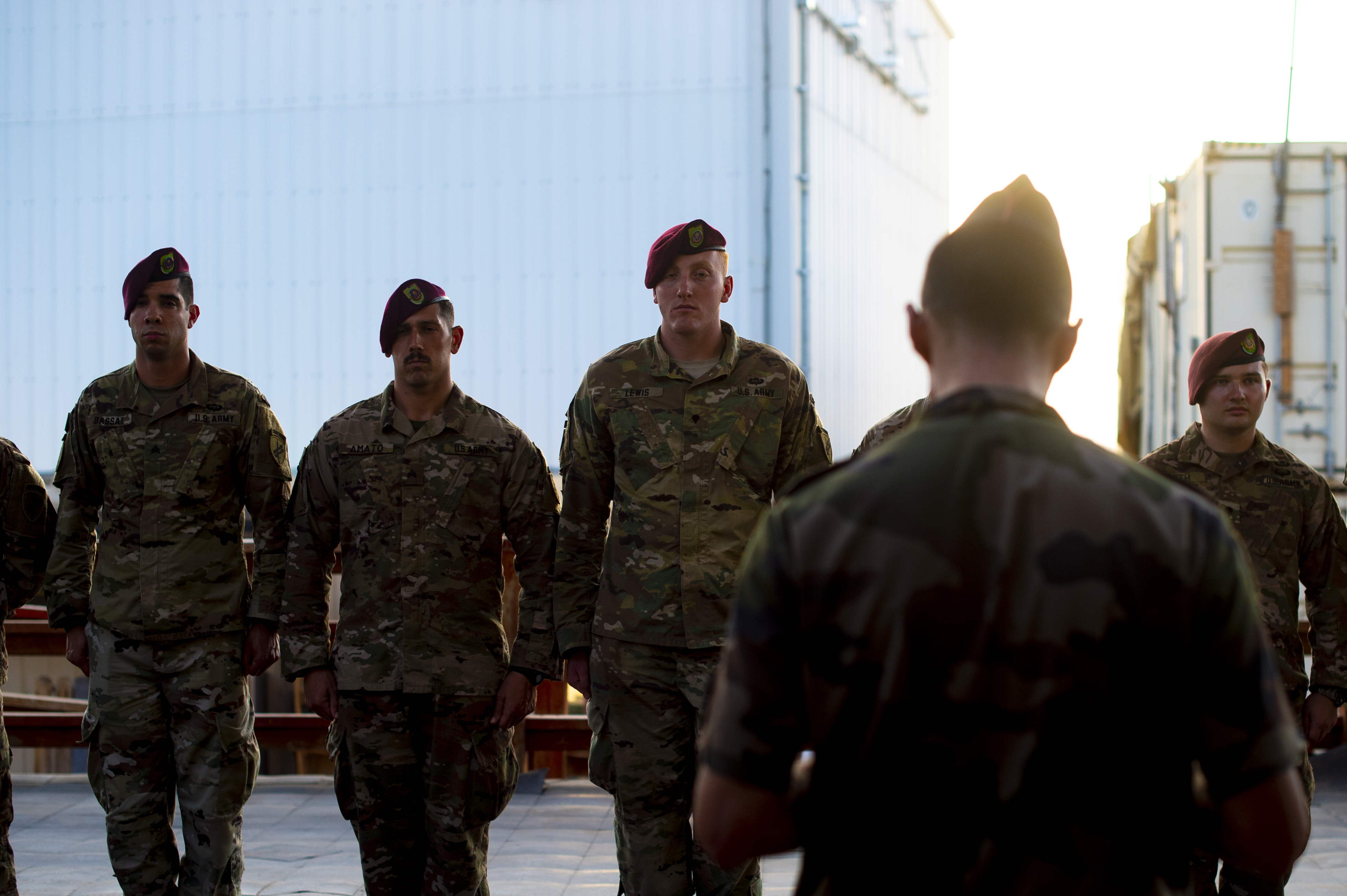 U.S. Army Soldiers of the 404th and 407th Civil Affairs teams stand together to receive their French Jump Wing badges from French jump masters on Camp Lemonnier, Djibouti, Oct. 1, 2018. The team members received their badges for jumping with the French in celebration of the Feast Day of Archangel Michael, the patron saint of paratroopers. (U.S. Air Force photo by Senior Airman Scott Jackson)
