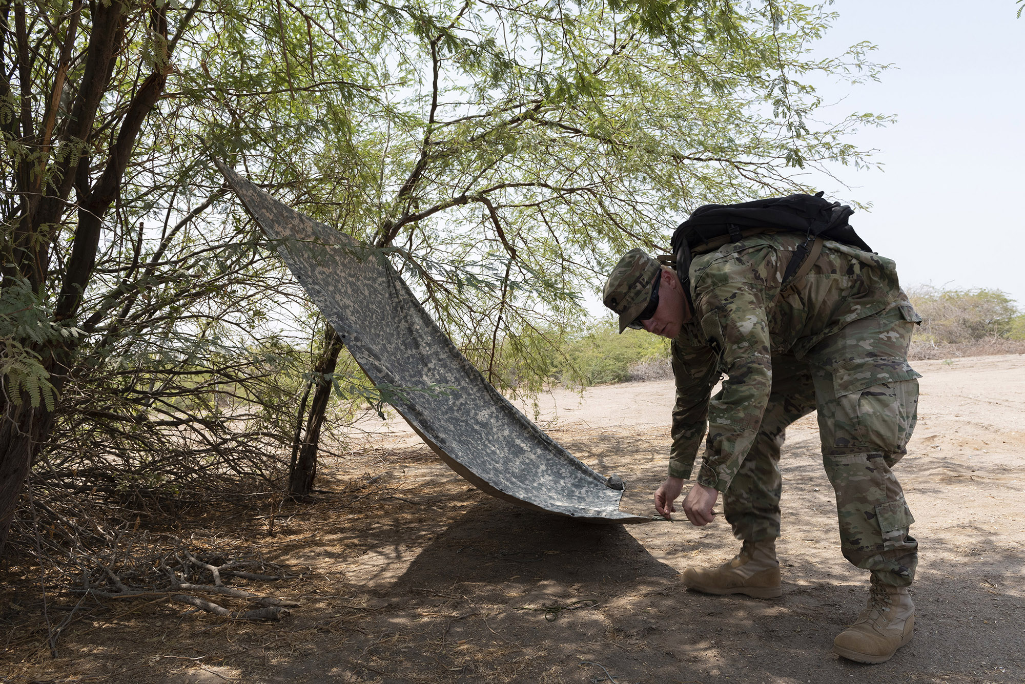U.S. Army Spec. Killian Tooke, a radar repairer with 3rd Battalion, 133rd Field Artillery Regiment, Texas National Guard, uses a poncho liner to create a shaded shelter during survival skills training on Camp Lemonnier, Djibouti, Oct. 13, 2018. During this training, Tooke completed various tasks such as constructing a shelter, finding alternative water sources and signaling for rescue. (U.S. Air National Guard photo by Master Sgt. Sarah Mattison)