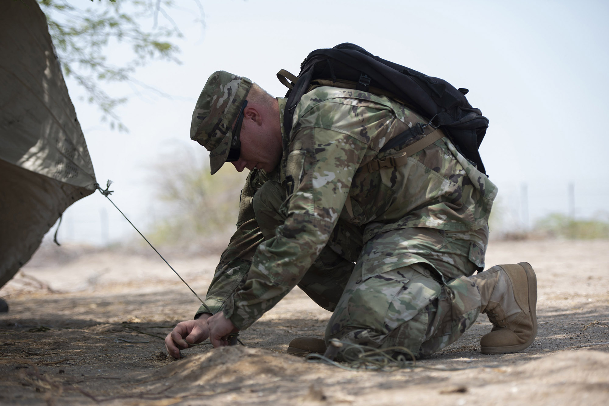 U.S. Army Spec. Killian Tooke, a radar repairer with 3rd Battalion, 133rd Field Artillery Regiment, Texas National Guard, ties down a poncho liner while creating a shade shelter during survival skills training on Camp Lemonnier, Djibouti, Oct. 13, 2018. During this training, Tooke completed various tasks such as constructing a shelter, finding alternative water sources and signaling for rescue. (U.S. Air National Guard photo by Master Sgt. Sarah Mattison)
