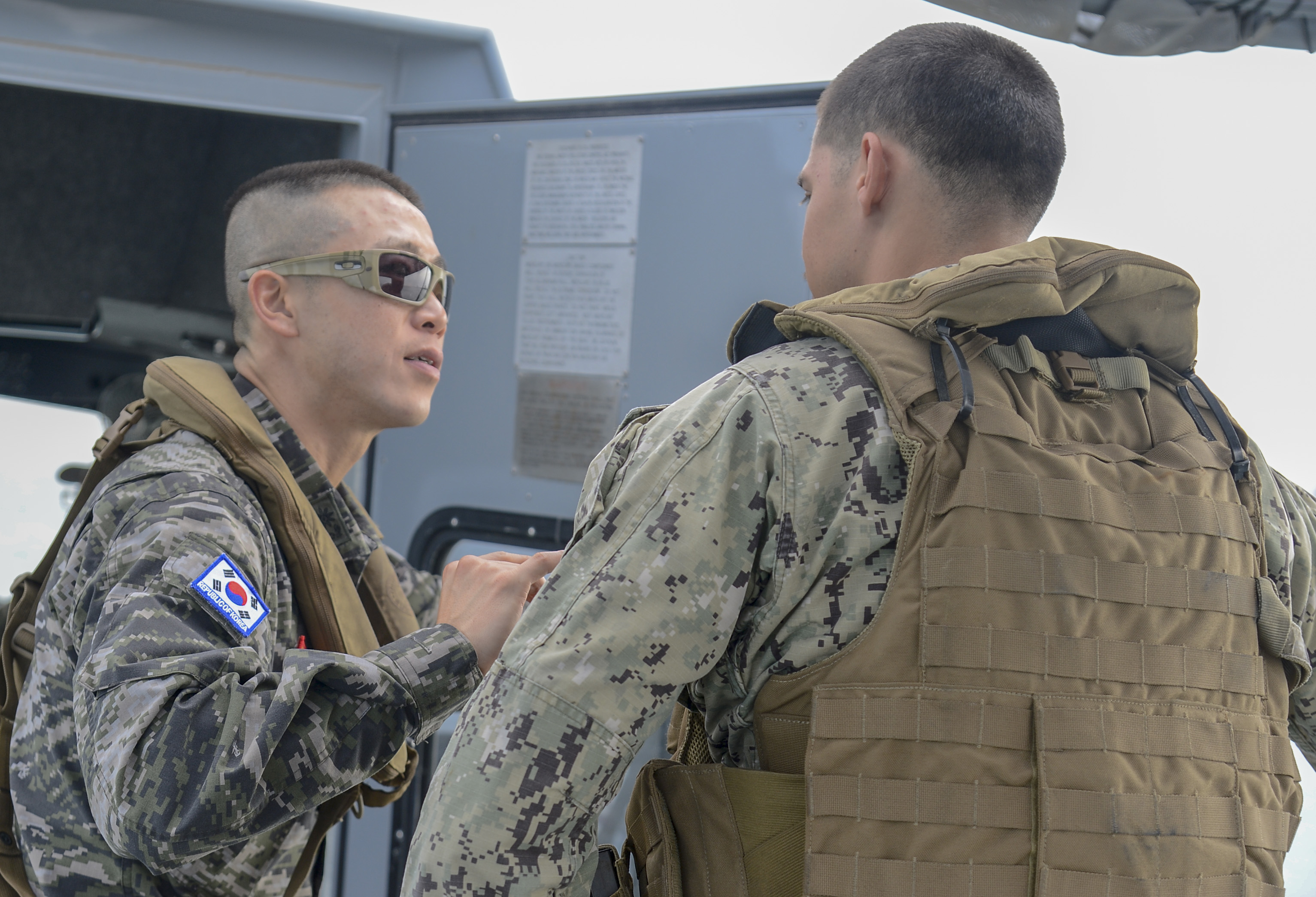 Republic of Korea marine Maj. Hyunchang Choi, a foreign liaison officer assigned to Combined Joint Task Force-Horn of Africa (CJTF-HOA), speaks to Master at Arms 3rd Class Daniel Ortiz, assigned to Coastal Riverine Squadron (CRS) 8, during maritime security operations (MSO) in the Gulf of Tadjourah, Oct. 23, 2018. CJTF-HOA FLOs observed the operations to better understand MSO and the CRS-8 mission. (U.S. Navy photo by Mass Communication Specialist 2nd Class Timothy M. Ahearn)
