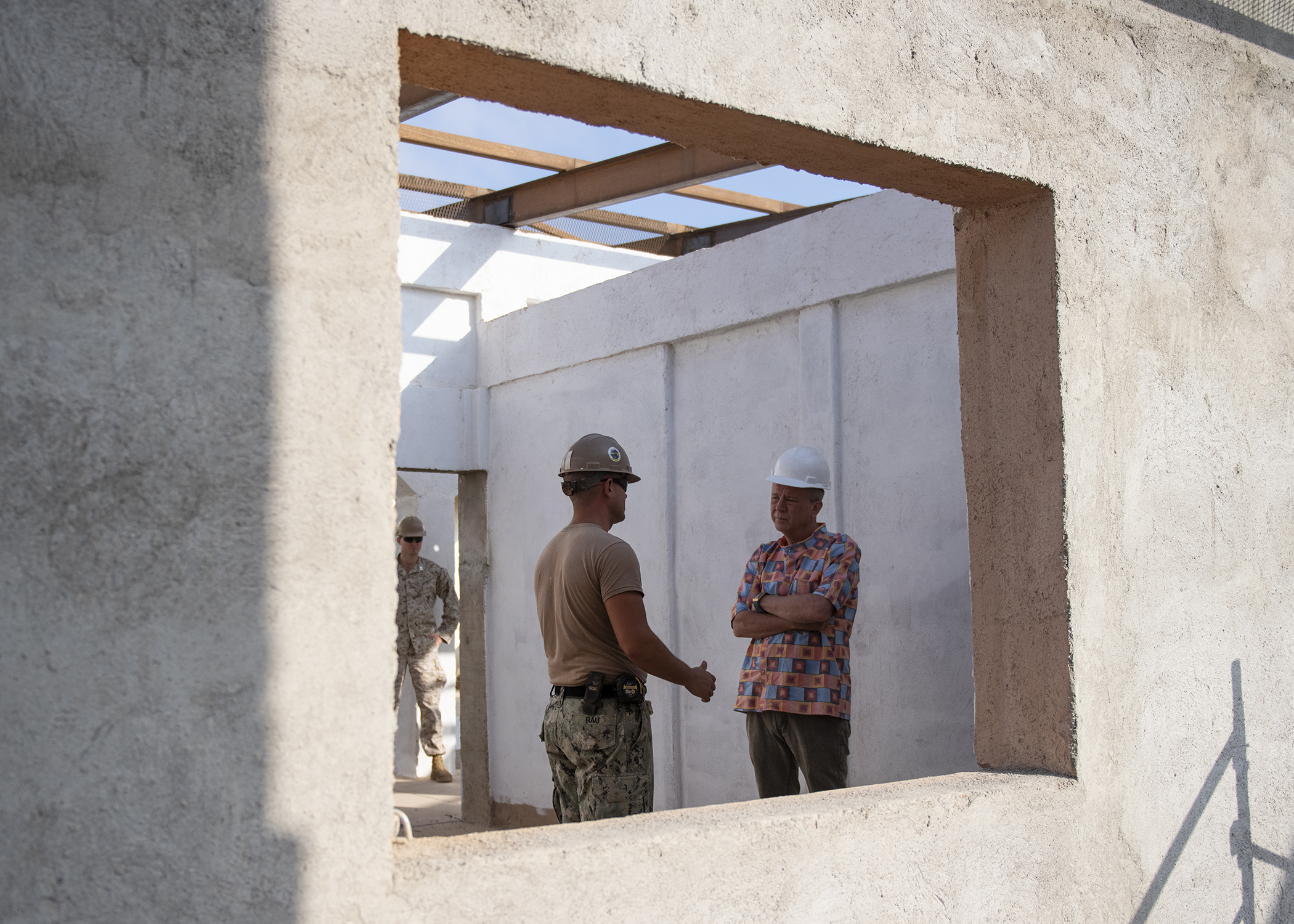 Amb. Larry André Jr., U.S. Ambassador to the Republic of Djibouti, speaks to a U.S. Navy Seabee, assigned to Combined Joint Task Force-Horn of Africa, Camp Lemonnier, Djibouti, during a visit to the construction site of the future Ali Oune, Djibouti, Women's Medical Clinic, Dec. 3, 2018. Slated for completion by January 2019, the clinic is intended to enhance the Ministry of Health for Djibouti's ability to provide basic medical, birth and after care to the Ali Oune village and its more than 1,000 residents and rural neighbors. (U.S. Air Force photo by Tech. Sgt. Shawn Nickel)