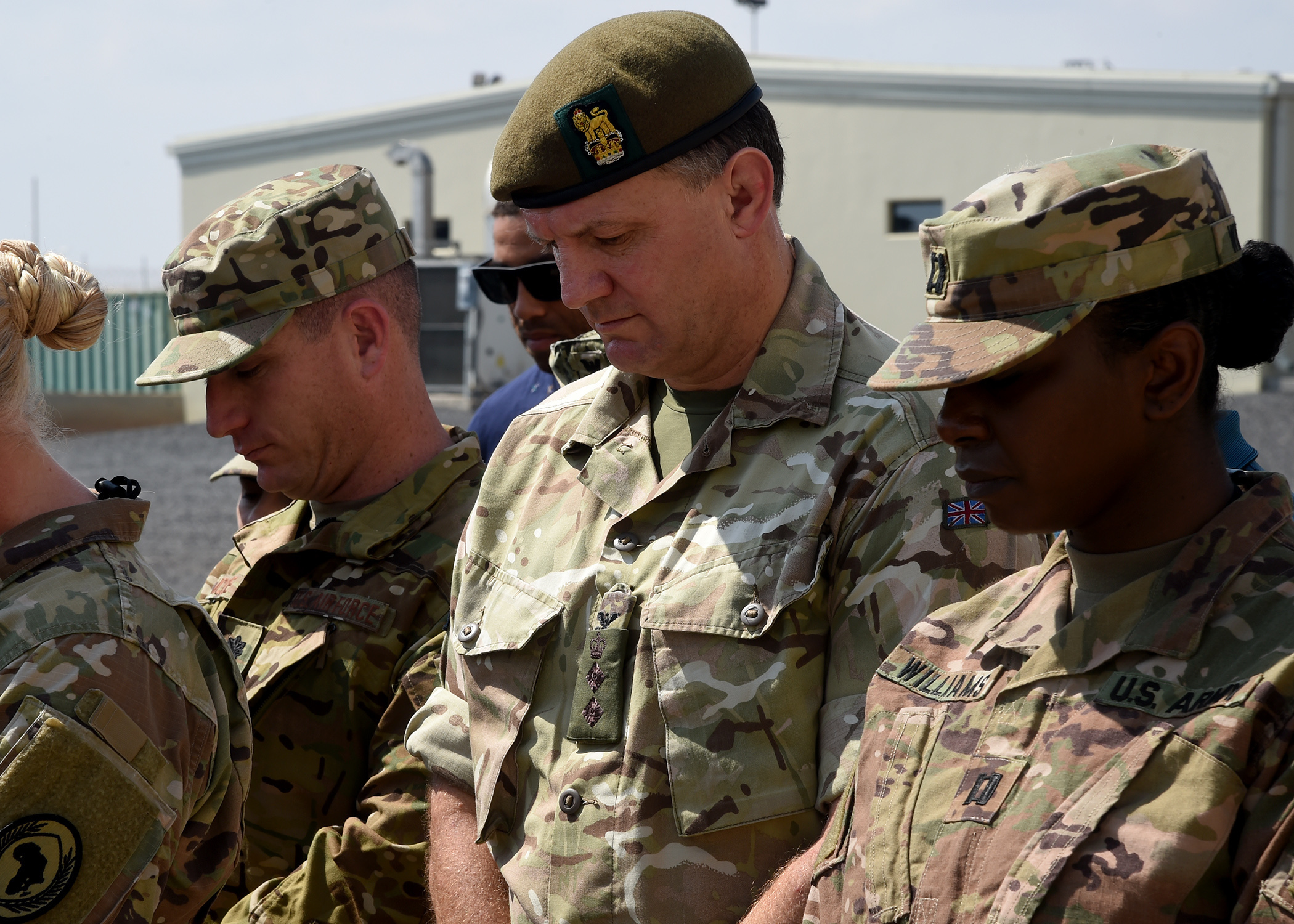 British Army Col. Simon Butt (center), Combined Joint Task Force-Horn of Africa plans and policy director, observes a moment of silence during a ceremony honoring the late U.S. President George H.W. Bush at Camp Lemonnier, Djibouti, Dec. 5, 2018. (U.S. Navy Photo by Mass Communication Specialist 1st Class Nick Scott/released)