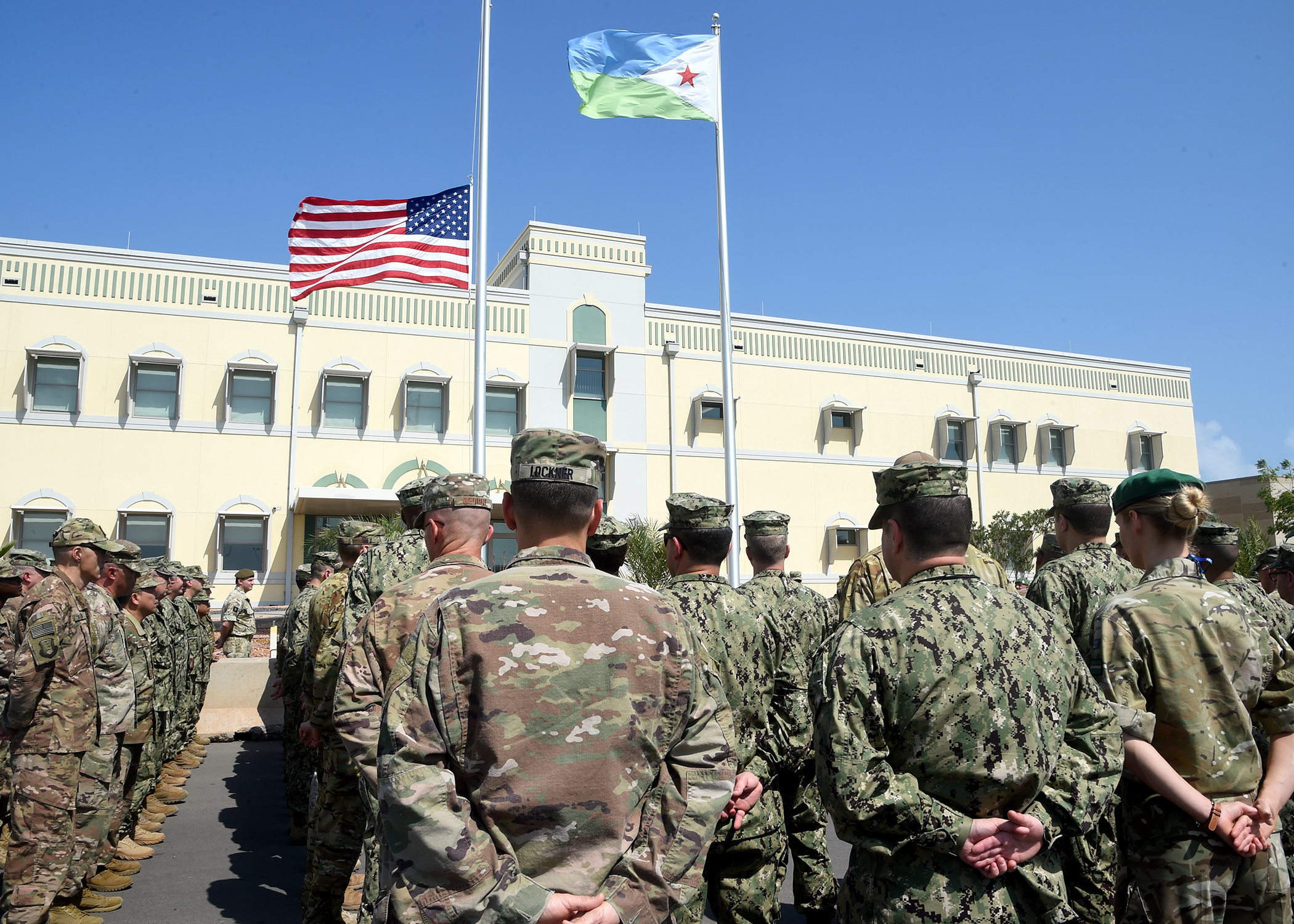 Joint forces from Combined Joint Task Force-Horn of Africa stand at parade rest during a ceremony honoring the late U.S. President George H.W. Bush at Camp Lemonnier, Djibouti, Dec. 5, 2018. (U.S. Navy Photo by Mass Communication Specialist 1st Class Nick Scott/released)