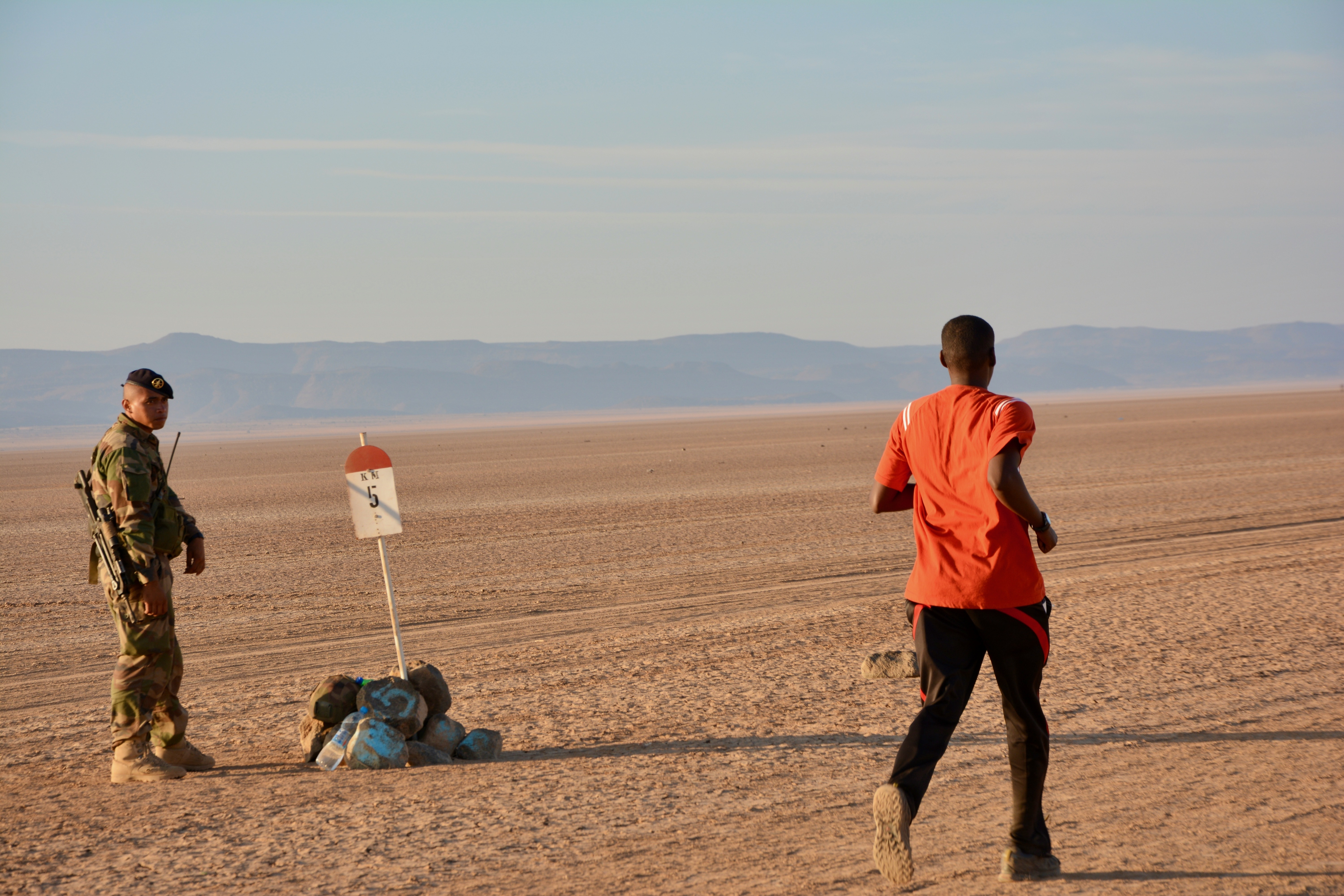 A runner approaches a kilometer marker during a 15-kilometer run through the Grand Bara Desert in Djibouti. Hosted by the French Foreign Legion, nearly 200 members of Combined Joint Task Force – Horn of Africa ran alongside 2,500 Djiboutian, Chinese, and coalition service members and civilians during the race across a stretch of Djibouti's Grand Bara Desert, Dec. 13. (U.S. Army photo by Capt. Olivia Cobiskey)