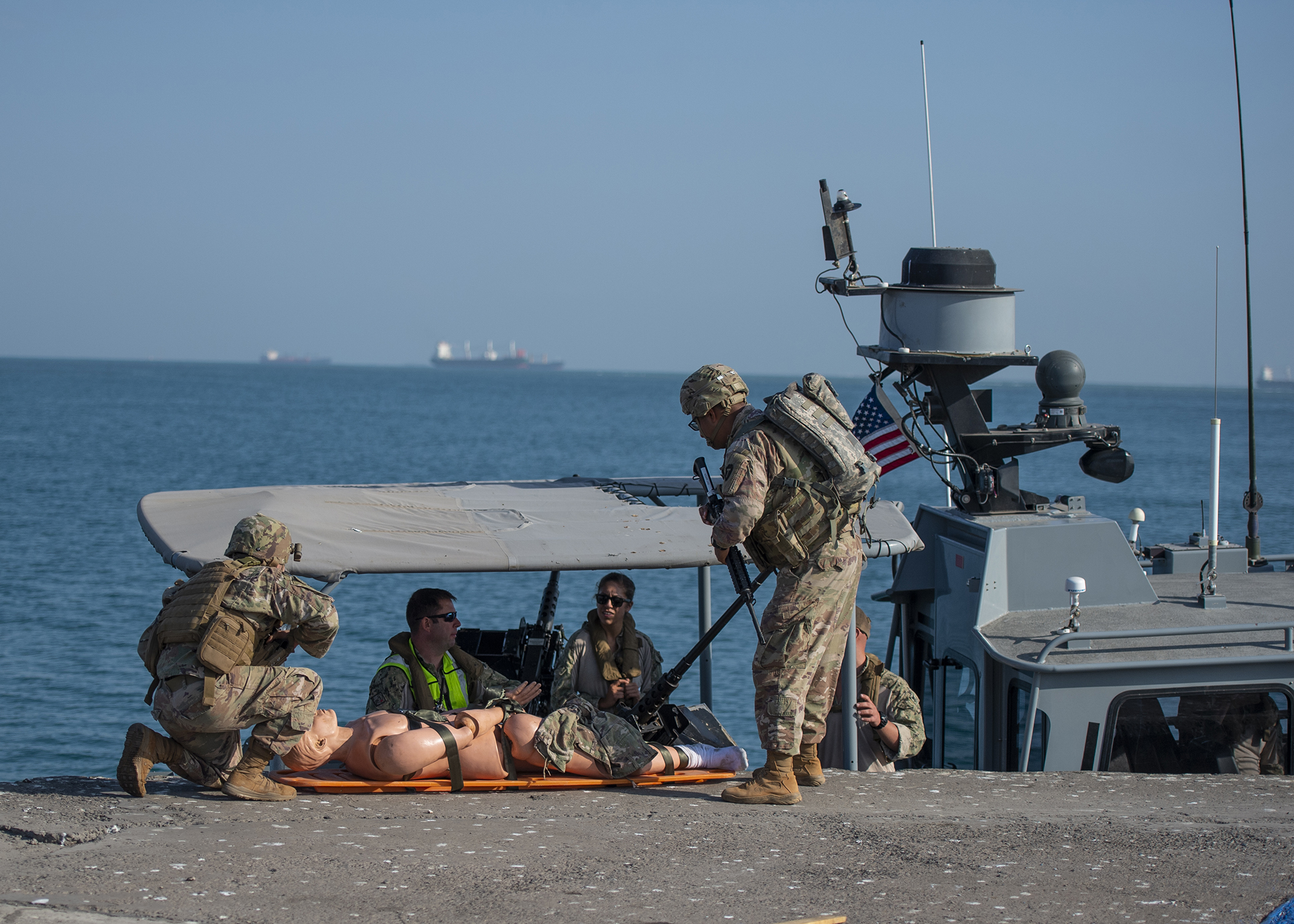 U.S. Army Soldiers from 1st Battalion, 141st Infantry Regiment, Task Force Alamo, Texas National Guard, deployed to Combined Joint Task Force-Horn of Africa (CJTF-HOA), Djibouti, receive a simulated casualty from U.S. Navy Sailors assigned to Coastal Riverine Squadron 8, CJTF-HOA, during the first-ever U.S. military exercise at the Port of Djibouti, Dec. 19, 2018. The casualty evacuation exercise tested response time in case of a combat injury and included U.S. Navy, Army and Djibouti Port Authority assets. (U.S. Air Force photo by Tech. Sgt. Shawn Nickel)