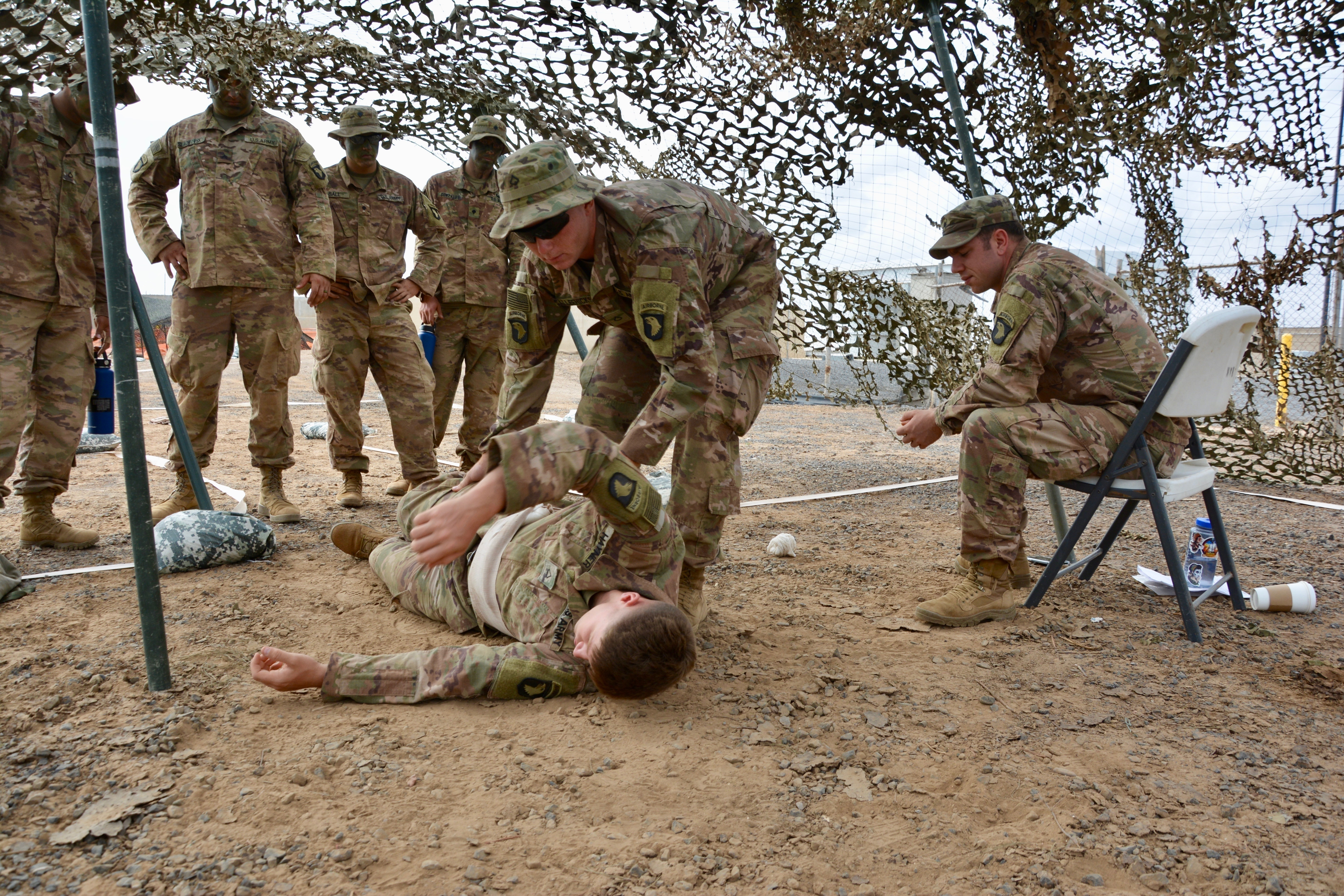 U.S. Army Pfc. Jessie Sallee-Hicks, assigned to Bravo Company, 1st Battalion, 26th Infantry Regiment, 101st Airborne Division, treats a Soldier for an abdominal wound and eye injuring during training for the Expert Infantryman Badge at Camp Lemonnier, Djibouti, Dec. 18, 2018. Members of the Fort Campbell, Kentucky unit demonstrated a mastery of critical skills that reinforce their ability to respond to emergency situations at U.S. Embassies in the East African region as members of the Combined Joint Task Force-Horn of Africa (CJTF-HOA), East Africa Response Force (EARF).