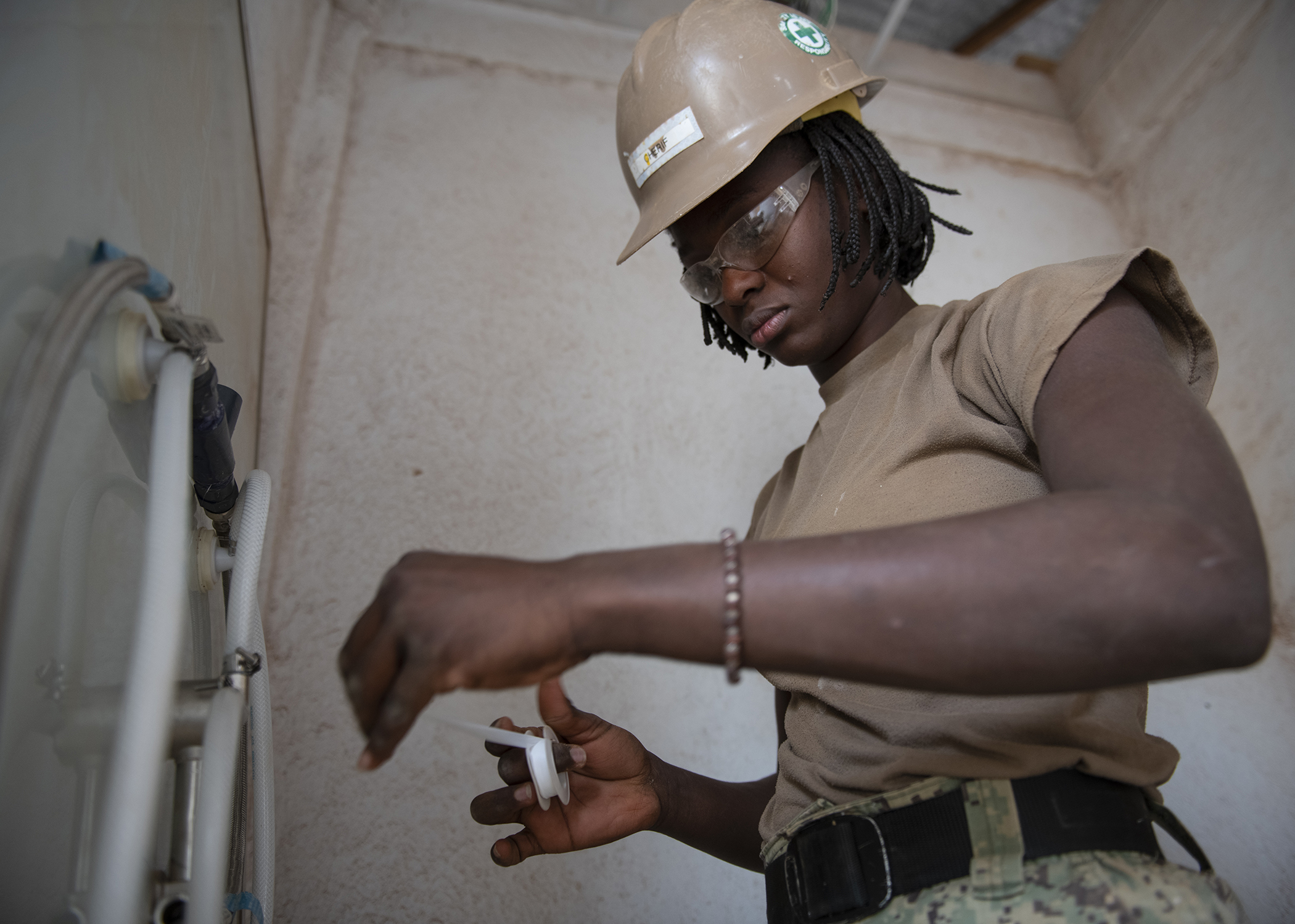 U.S. Navy Seaman Mariame Cherif, a Seabee assigned to Naval Mobile Construction Battalion 1, Combined Joint Task Force-Horn of Africa, Camp Lemonnier, Djibouti, installs shower plumbing during the construction of the future Ali Oune, Djibouti, Women's Medical Clinic, Dec. 27, 2018. Cherif speaks six languages and acts as the battalion's translator, utilizing her French speaking skill. The clinic is intended to enhance the Ministry of Health for Djibouti's ability to provide basic medical, birth and after care to the Ali Oune village and its more than 1,000 residents and rural neighbors. (U.S. Air Force photo by Tech. Sgt. Shawn Nickel)