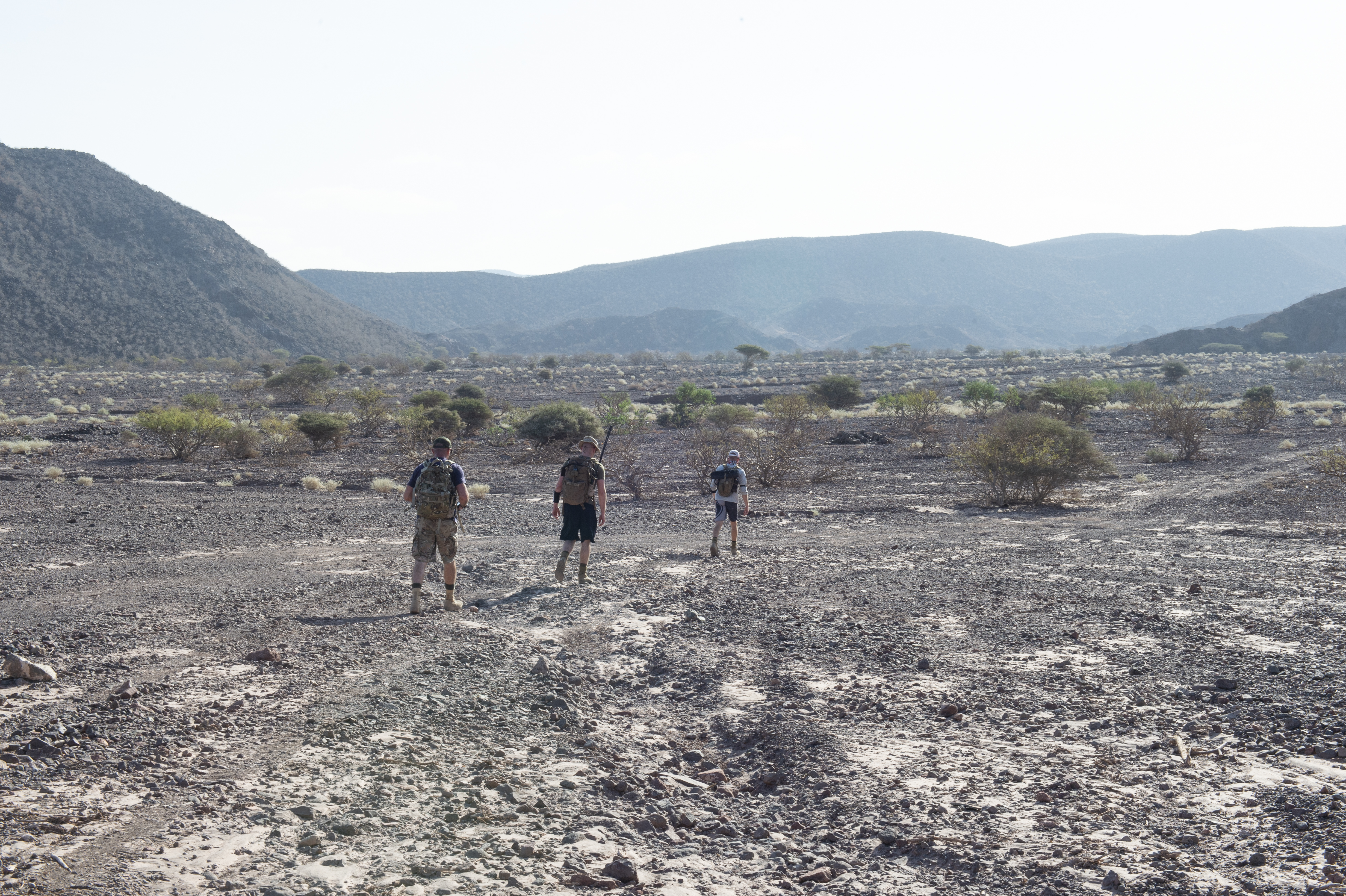 Tactical communication experts assigned to Combined Joint Task Force-Horn of Africa hike through a dry river bed on the way to a distant peak to test radio equipment during an exercise at the Arta Range Complex Jan. 18, 2019. The joint teams of Soldiers, Sailors and Marines utilized the exercise to test all forms of radio equipment they could be tasked to use in case of a last-minute forward deployment. (U.S. Air Force photo by Tech. Sgt. Shawn Nickel)