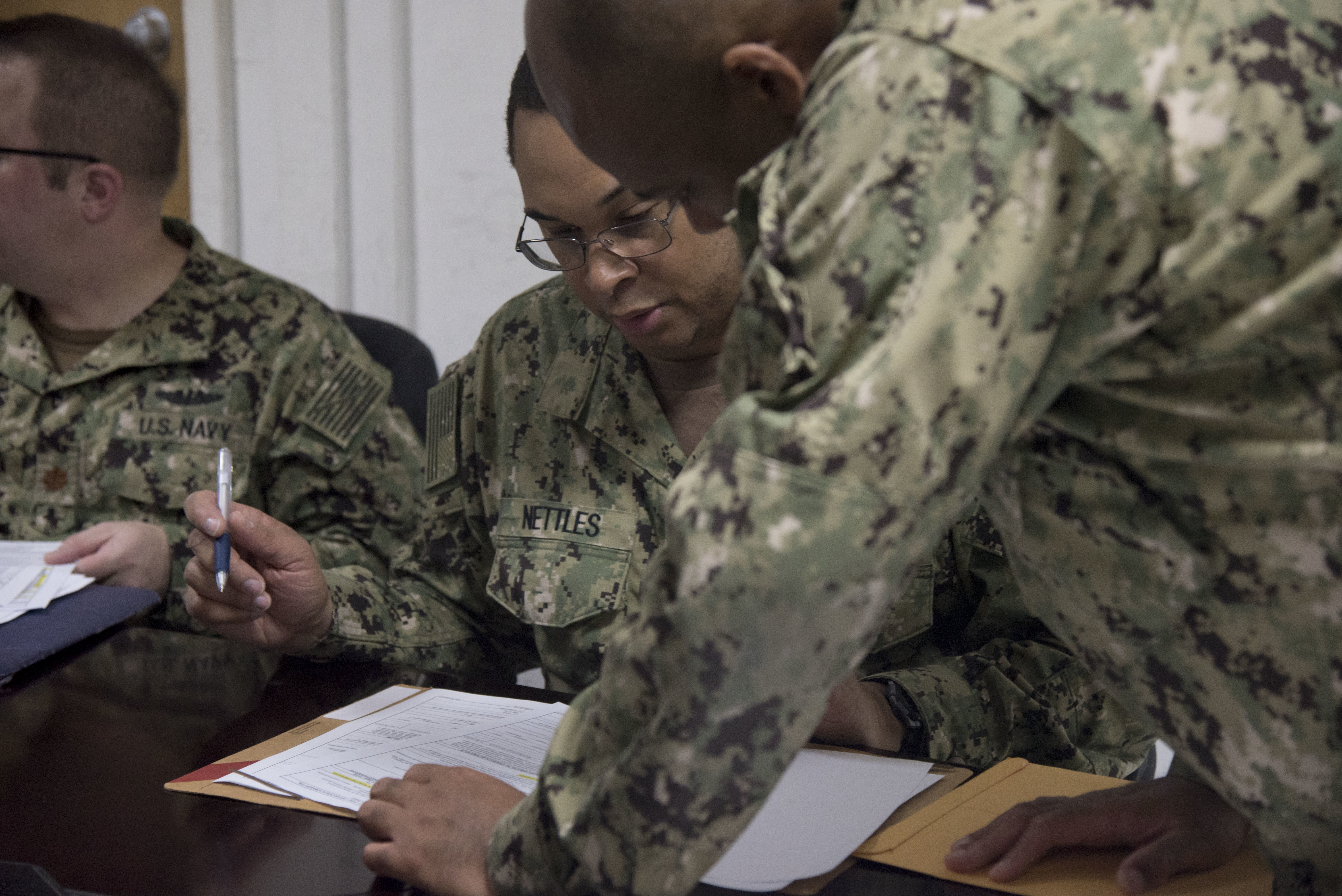 U.S. Navy Petty Officer 2nd Class Michael Roseborough, a personnel specialist with the Joint Personnel Center (JPC) assigned to Combined Joint Task Force-Horn of Africa, assists U.S. Navy Cmdr. Chris Nettles, incoming deputy director of communications for CJTF-HOA, in filling out entitlements paperwork at a mass in-processing briefing at Camp Lemonnier, Djibouti, Jan. 25, 2019. Mass in-processing briefings are just one of the tasks the JPC undertakes for Combined Joint Task Force-Horn of Africa. (U.S. Air Force photo by Senior Airman Kirsten Brandes)
