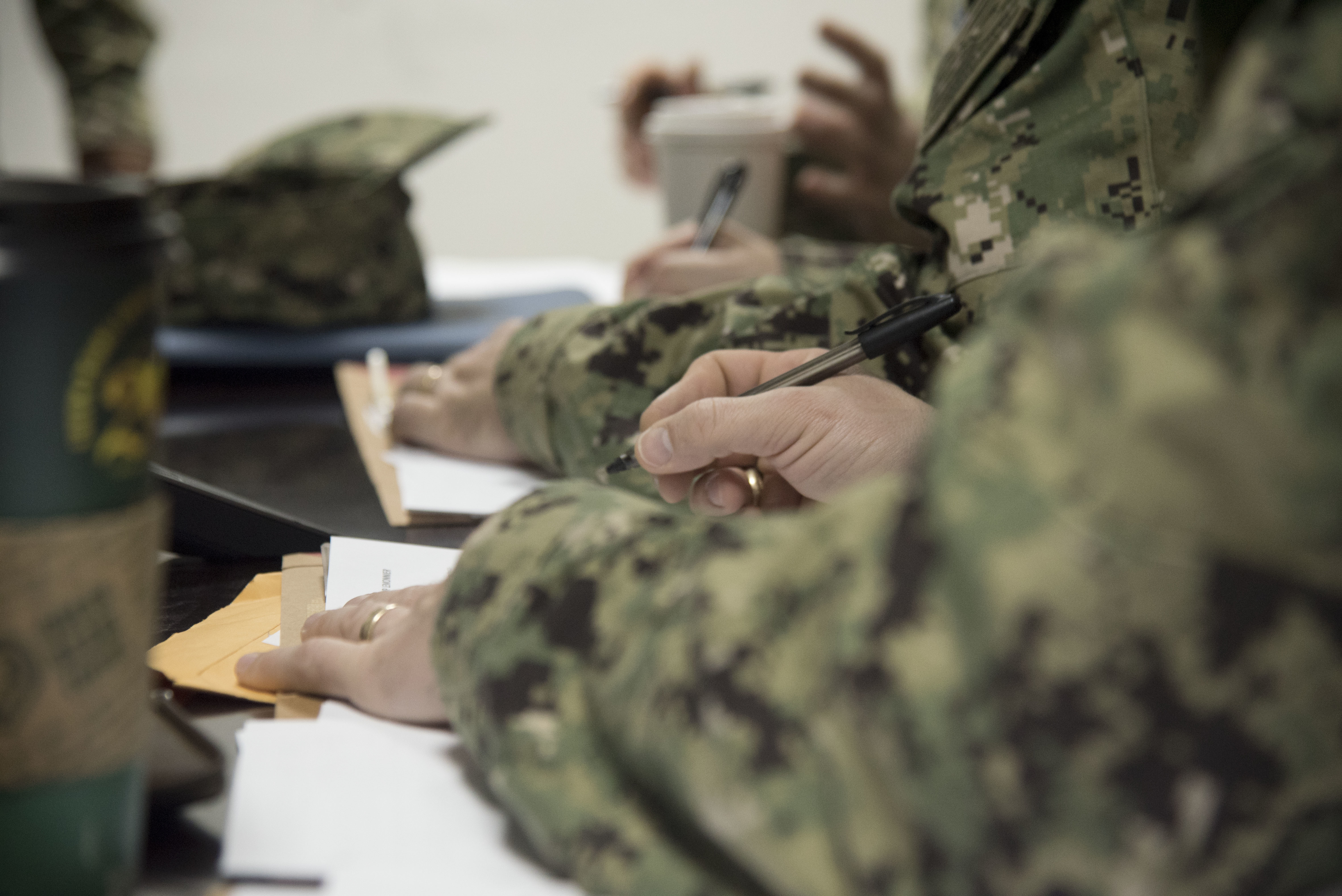 Recently-deployed Sailors complete in-processing paperwork at a mass in-processing briefing at Camp Lemonnier, Djibouti, Jan. 25, 2019. The Combined Joint Task Force-Horn of Africa's Joint Personnel Center conducts mass in-processing briefings to help Sailors complete paperwork that allows them to receive deployment benefits such as pay entitlements. (U.S. Air Force photo by Senior Airman Kirsten Brandes)